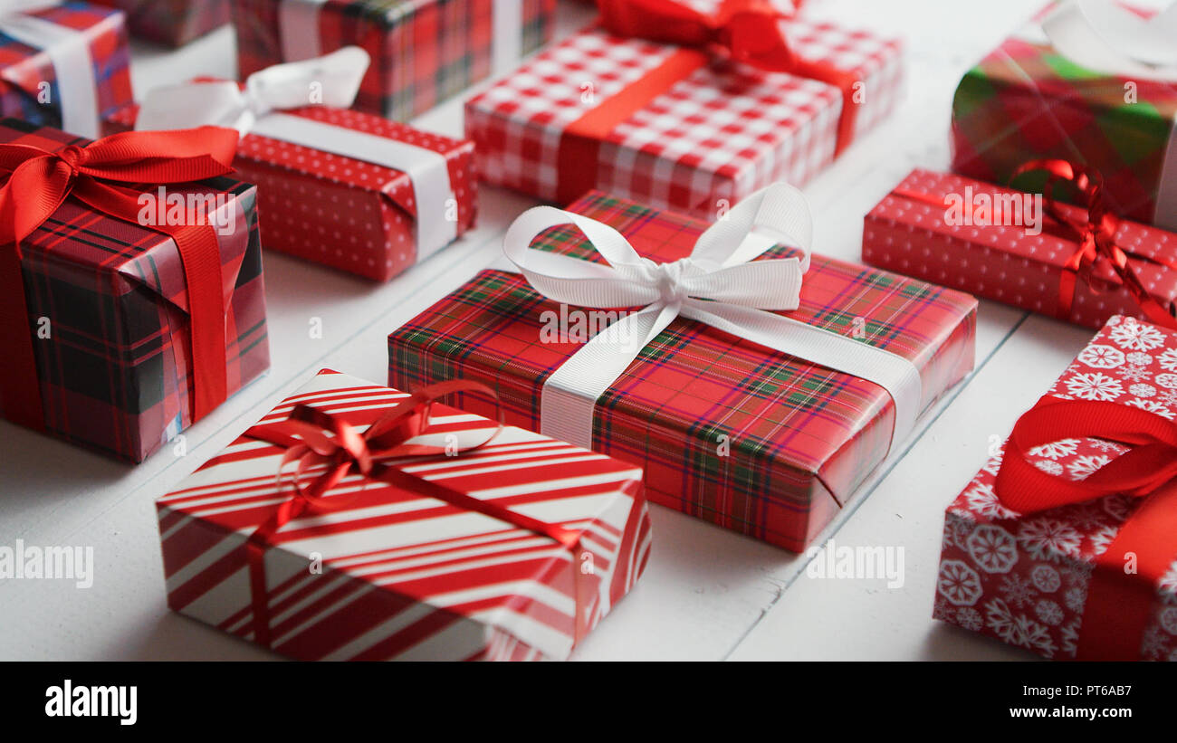 Side view of wrapped Christmas presents laid on the wooden table - Stock Image