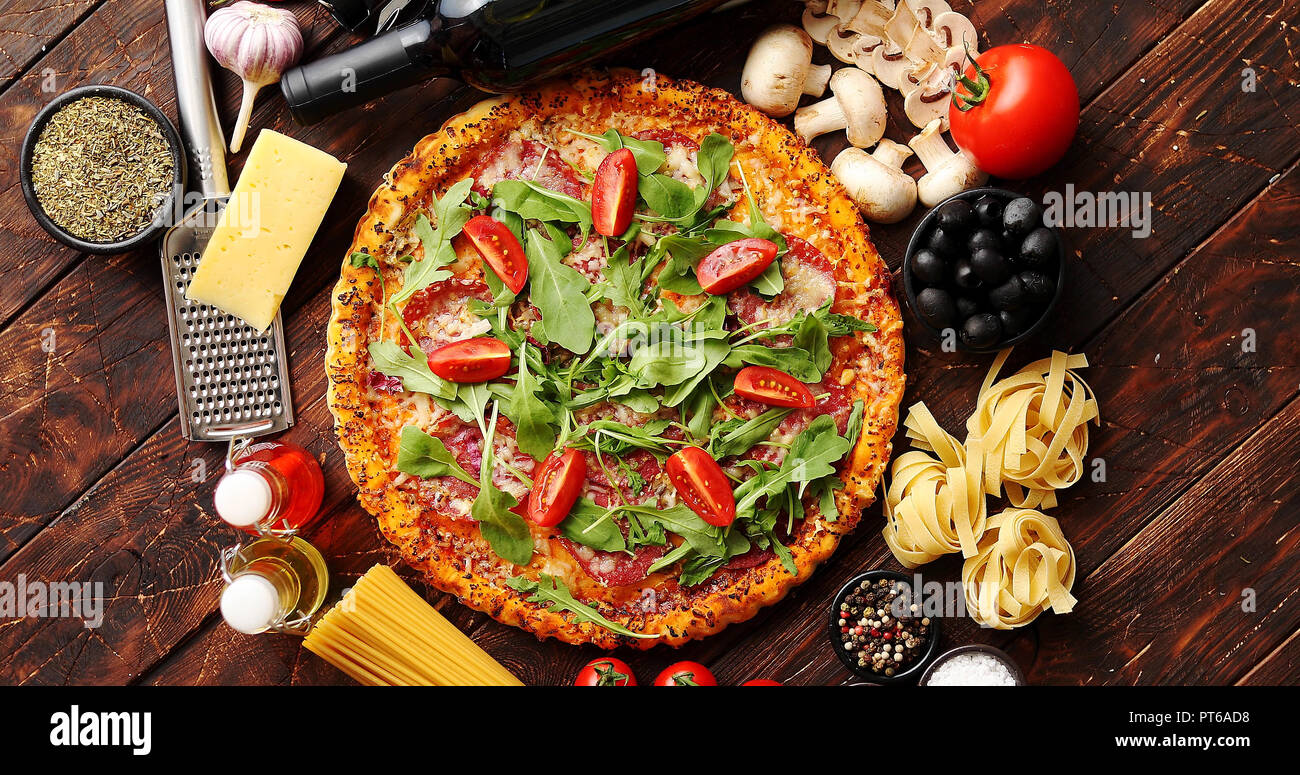 Italian food background with pizza, raw pasta and vegetables on wooden table - Stock Image