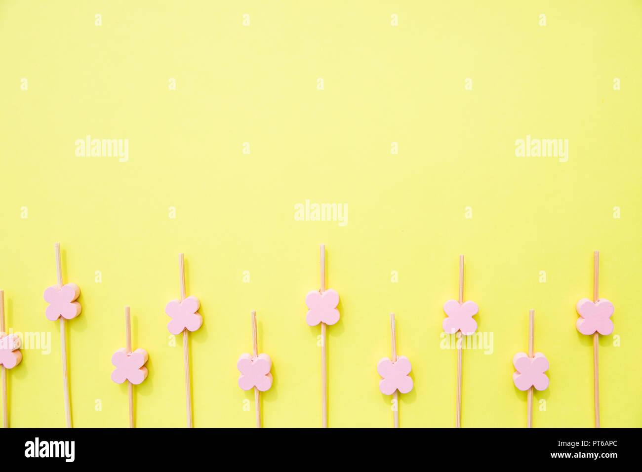 Ecological skewer isolated on yellow background.wooden sticks with flower beads for food decoration. Skewers for the preparation of canapes. Props for snack food.Copy space - Stock Image