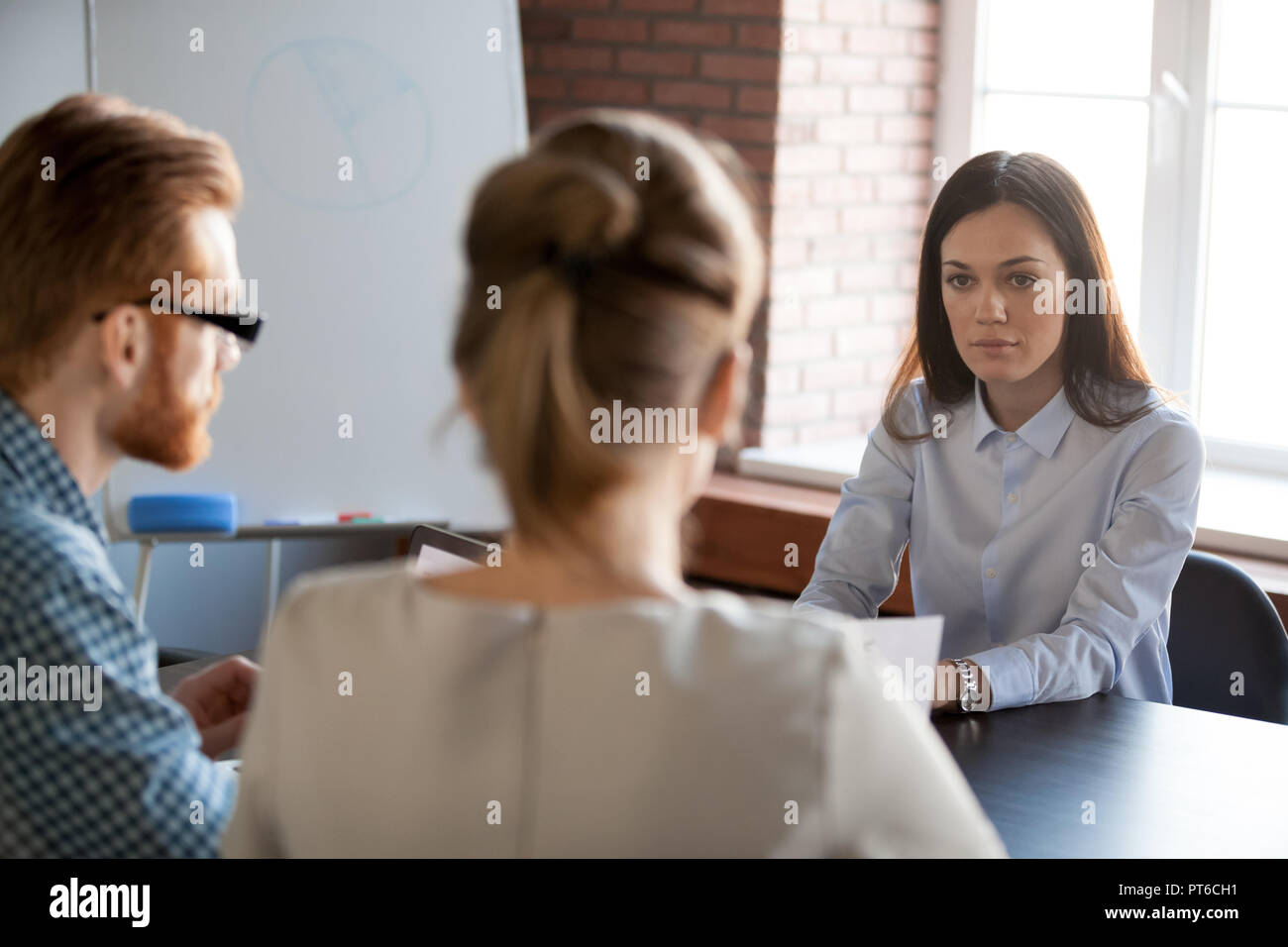 Serious female boss listening to employees reporting about work  - Stock Image
