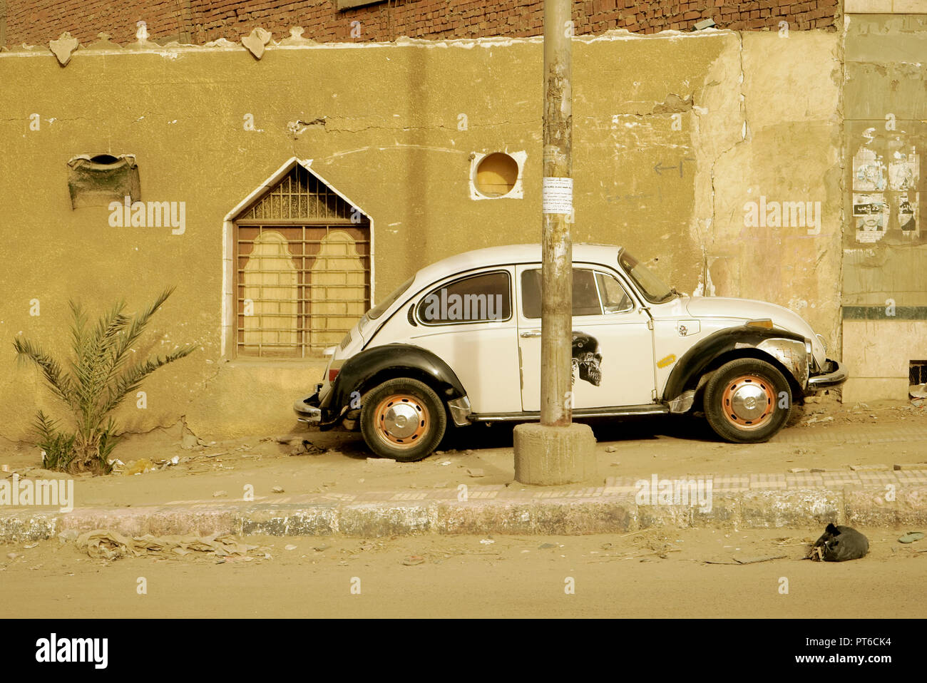 Old black and white Volkswagen Beetle parked on the side walk of a street of Aswan, Egypt. Stock Photo
