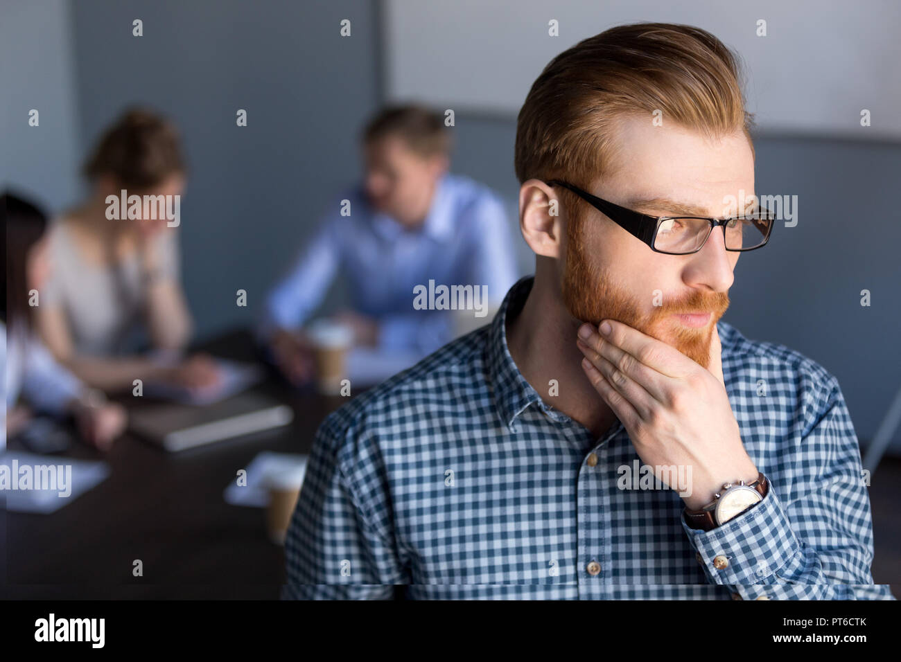 Thoughtful businessman looking away holding hand on chin plannin - Stock Image