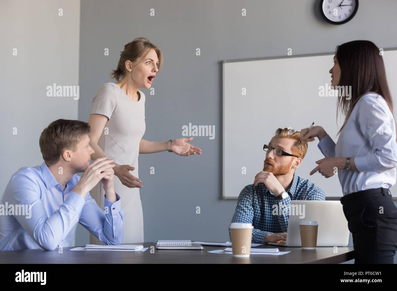 Businesswomen colleagues disputing at corporate office meeting,  - Stock Image
