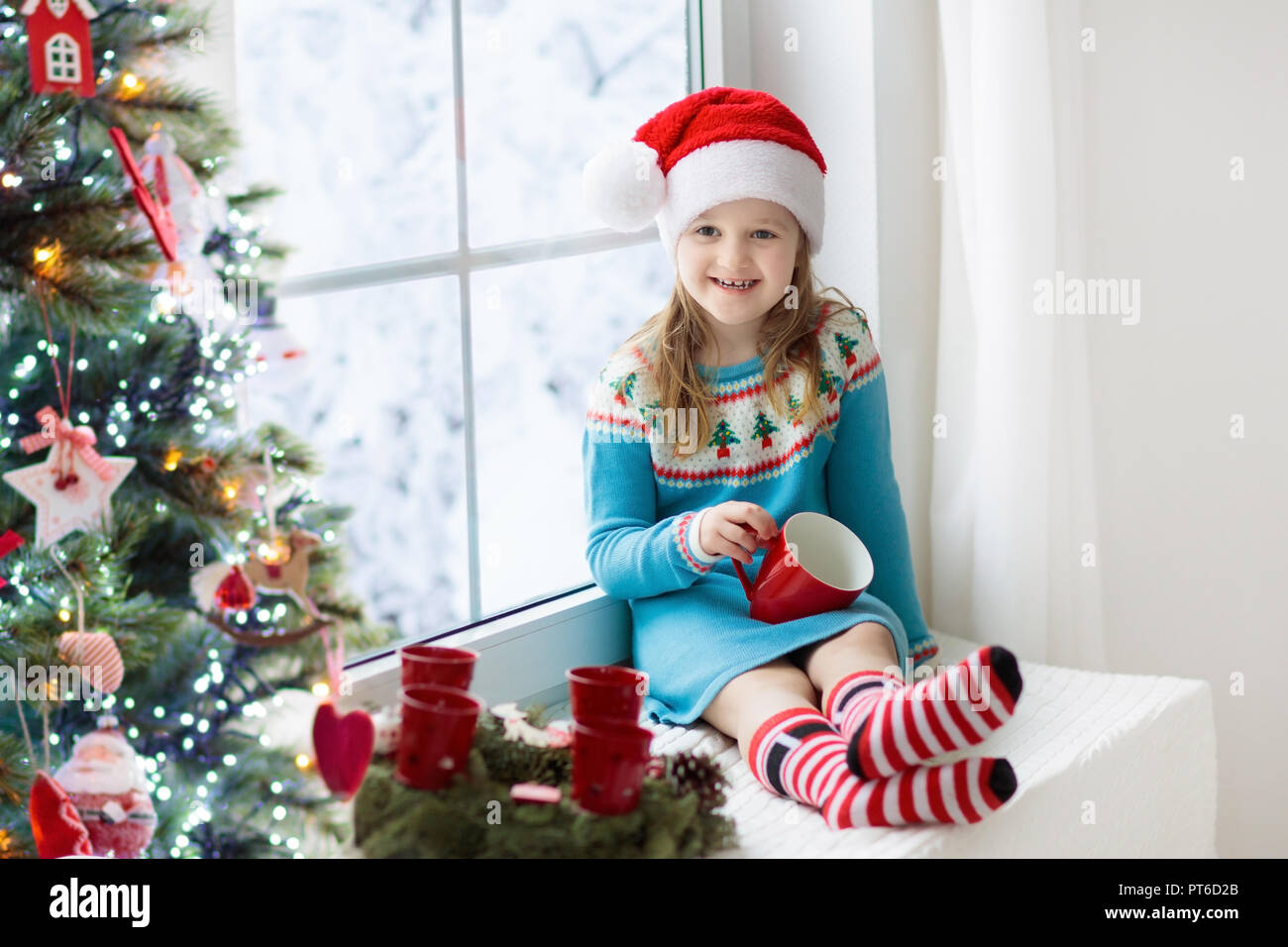 e2ab8316c24b Child drinking hot chocolate at Christmas tree at home. Decorated ...