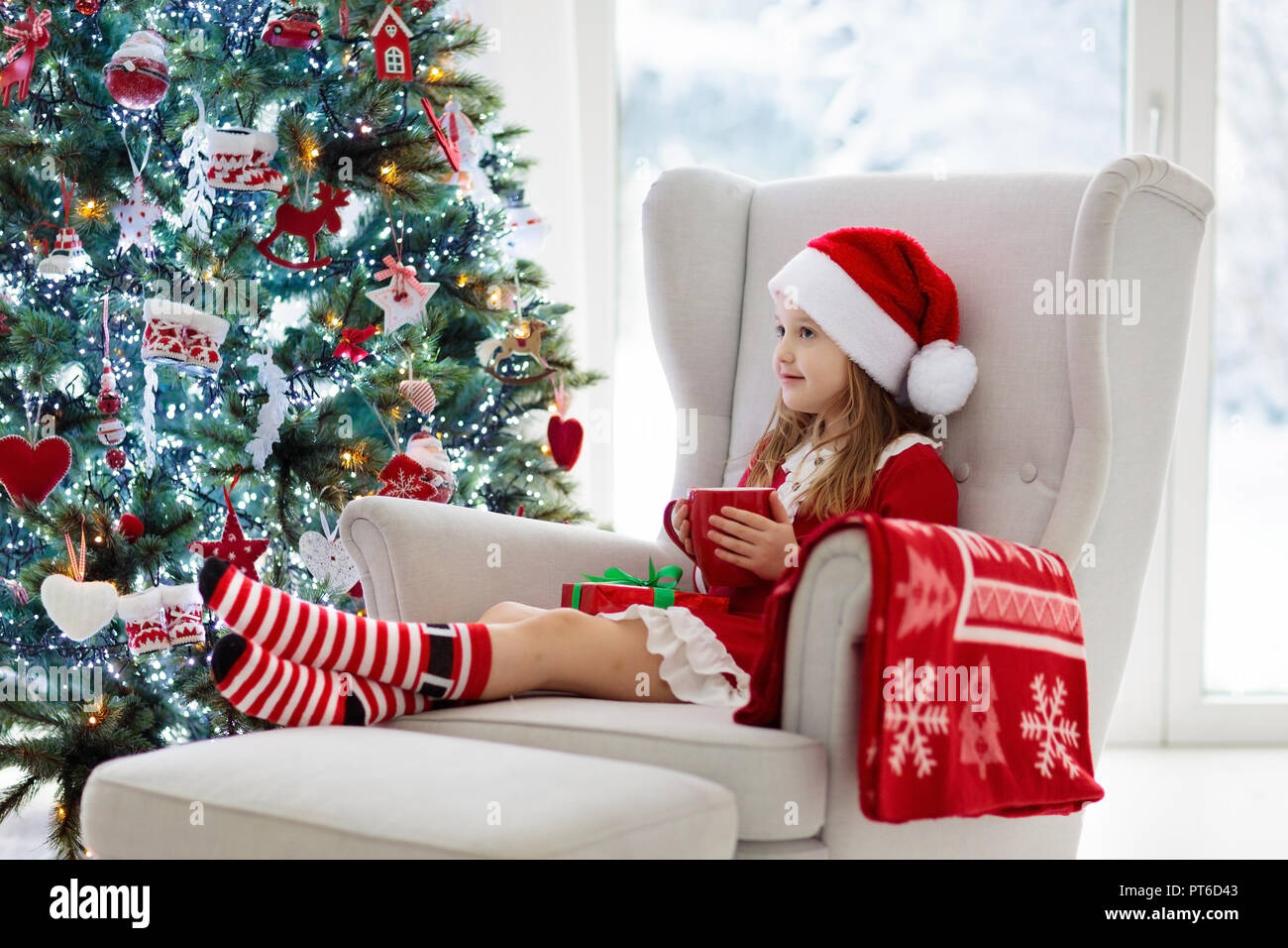 Child drinking hot chocolate at Christmas tree at home. Kid opening ...