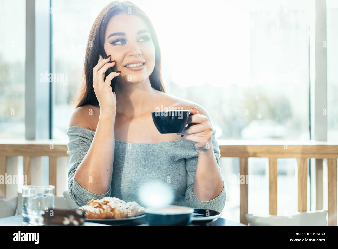 Beautiful woman holding blue cup of coffee and talking by mobile phone. - Stock Image
