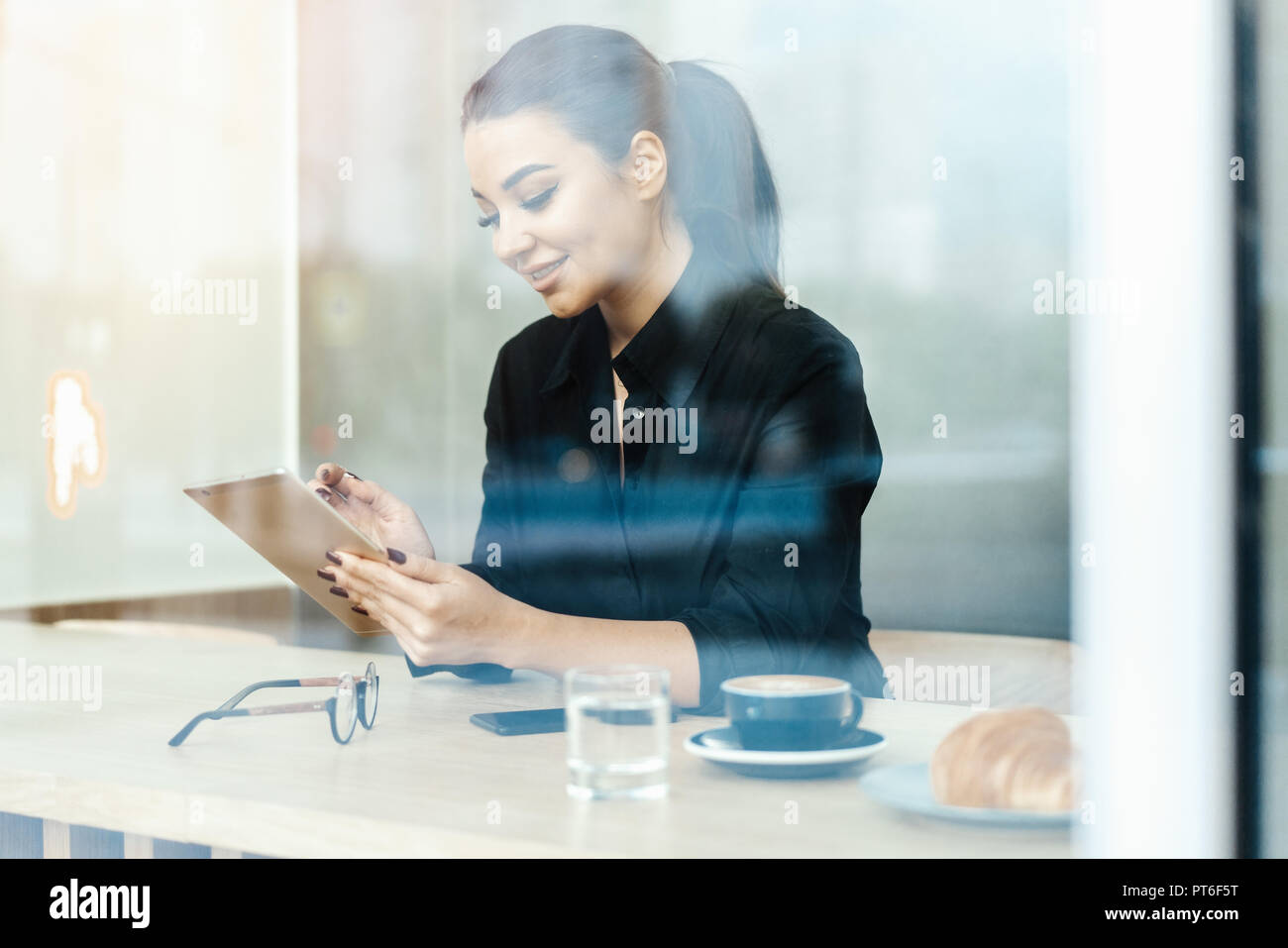 Close up of young beautiful brunette woman in cafe holding tablet and smiling. - Stock Image