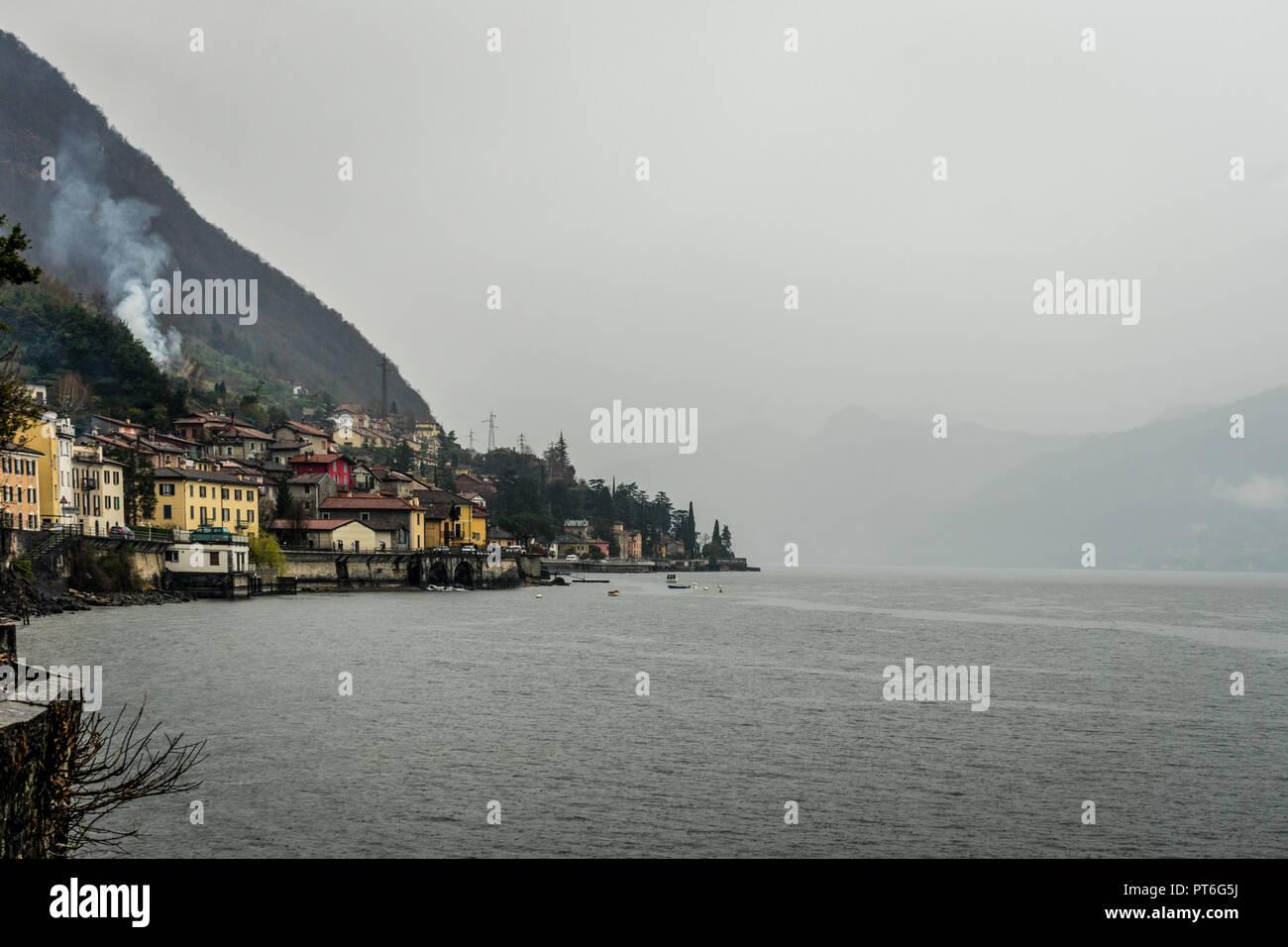 Italy, Varenna, Lake Como, fishing village viewed across lake - Stock Image