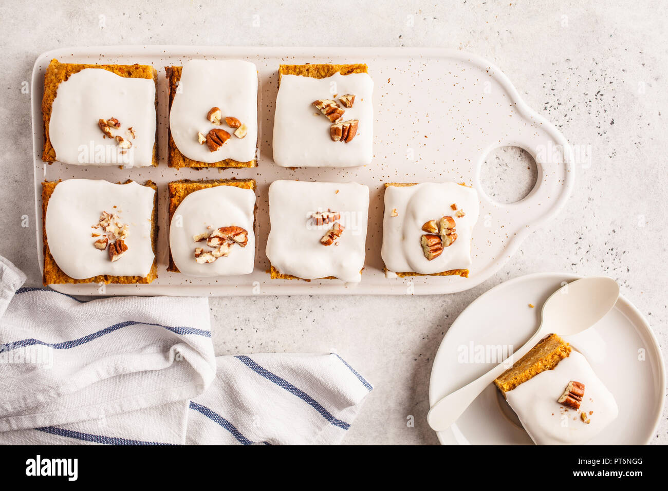 Vegan carrot cake with coconut cream and pecans on white board. Clean eating, healthy food, plant based diet concept. - Stock Image