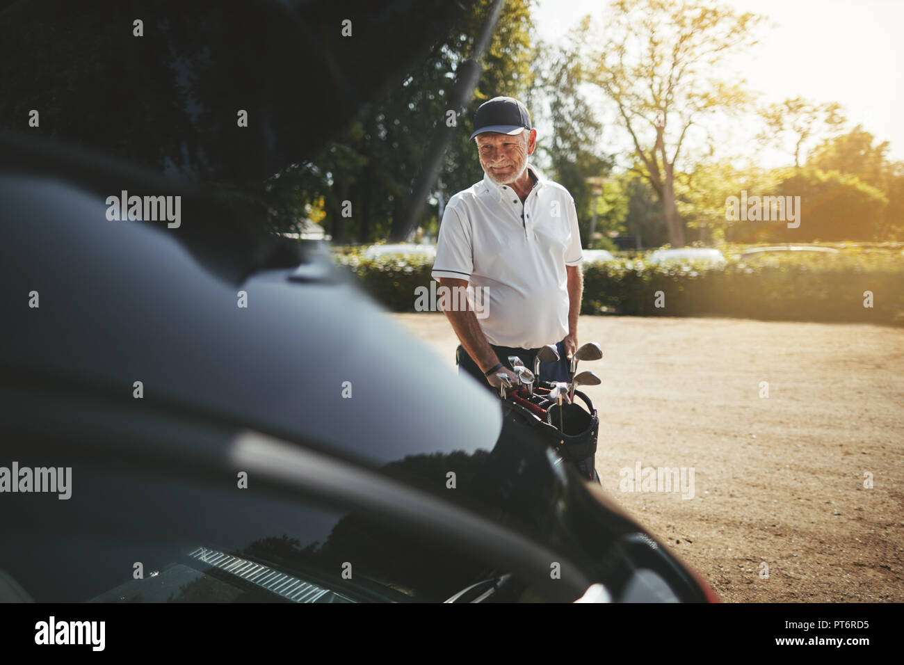 Sporty senior man smiling while packing his clubs into the trunk of his car after playing a round of golf on a sunny afternoon - Stock Image