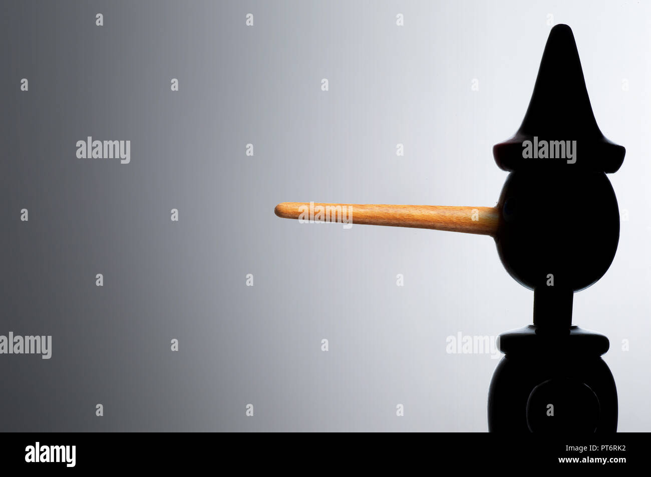 Concept Pinocchio Doll Figure in Silhouette, showing a Long Nose, Lie, Lying, Un trust wording - Stock Image