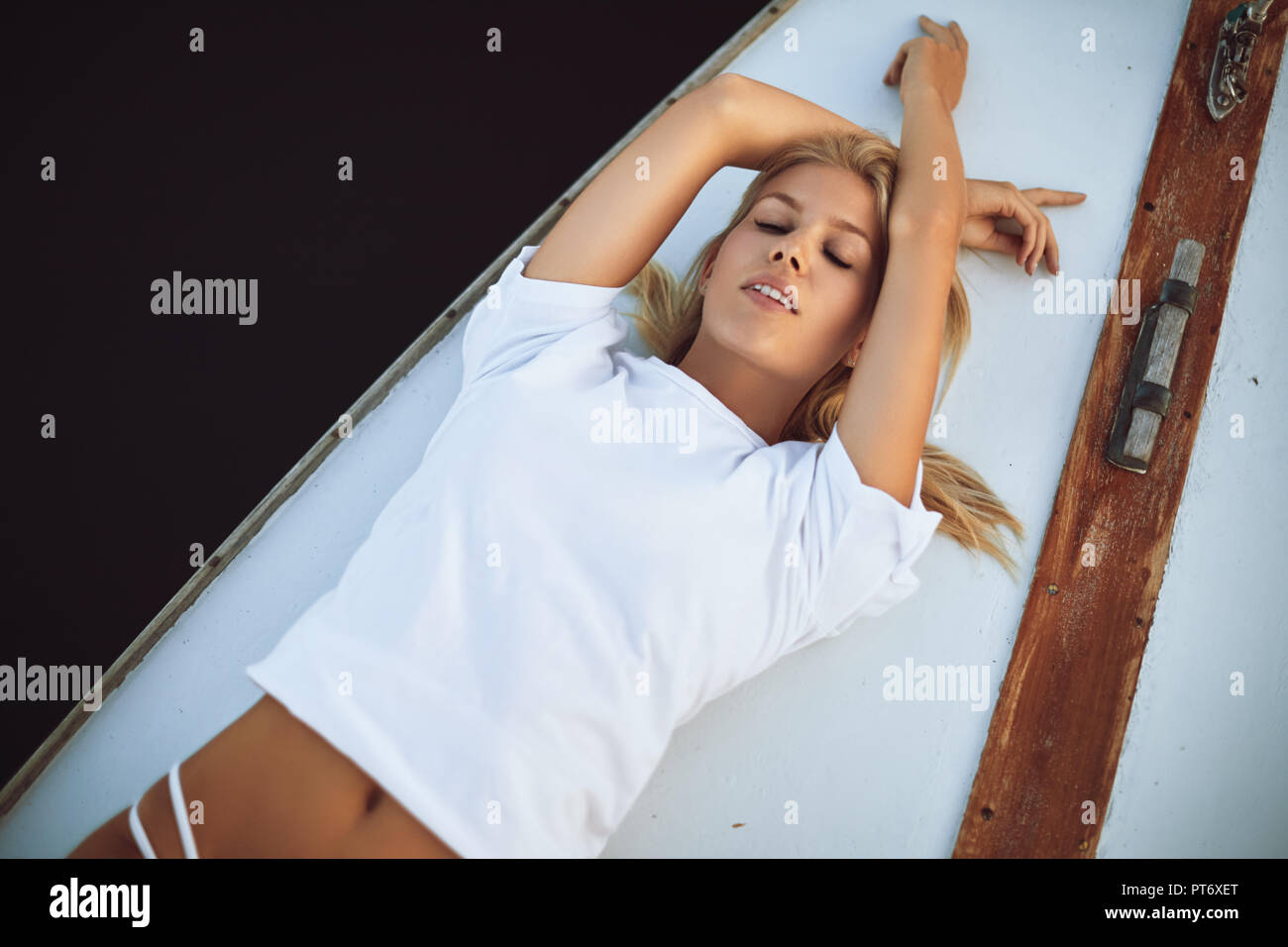 Attractive young woman in a bikini bottom and shirt suntanning while lying with her eyes closed on the deck of a yacht - Stock Image