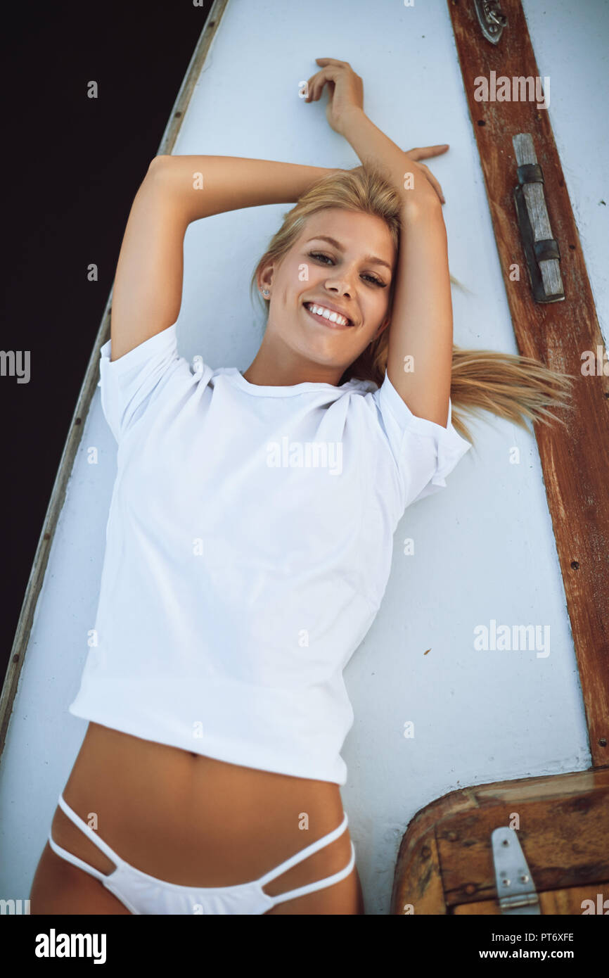 Attractive young woman in a bikini bottom and shirt lying on the deck of a yacht catching a suntan - Stock Image