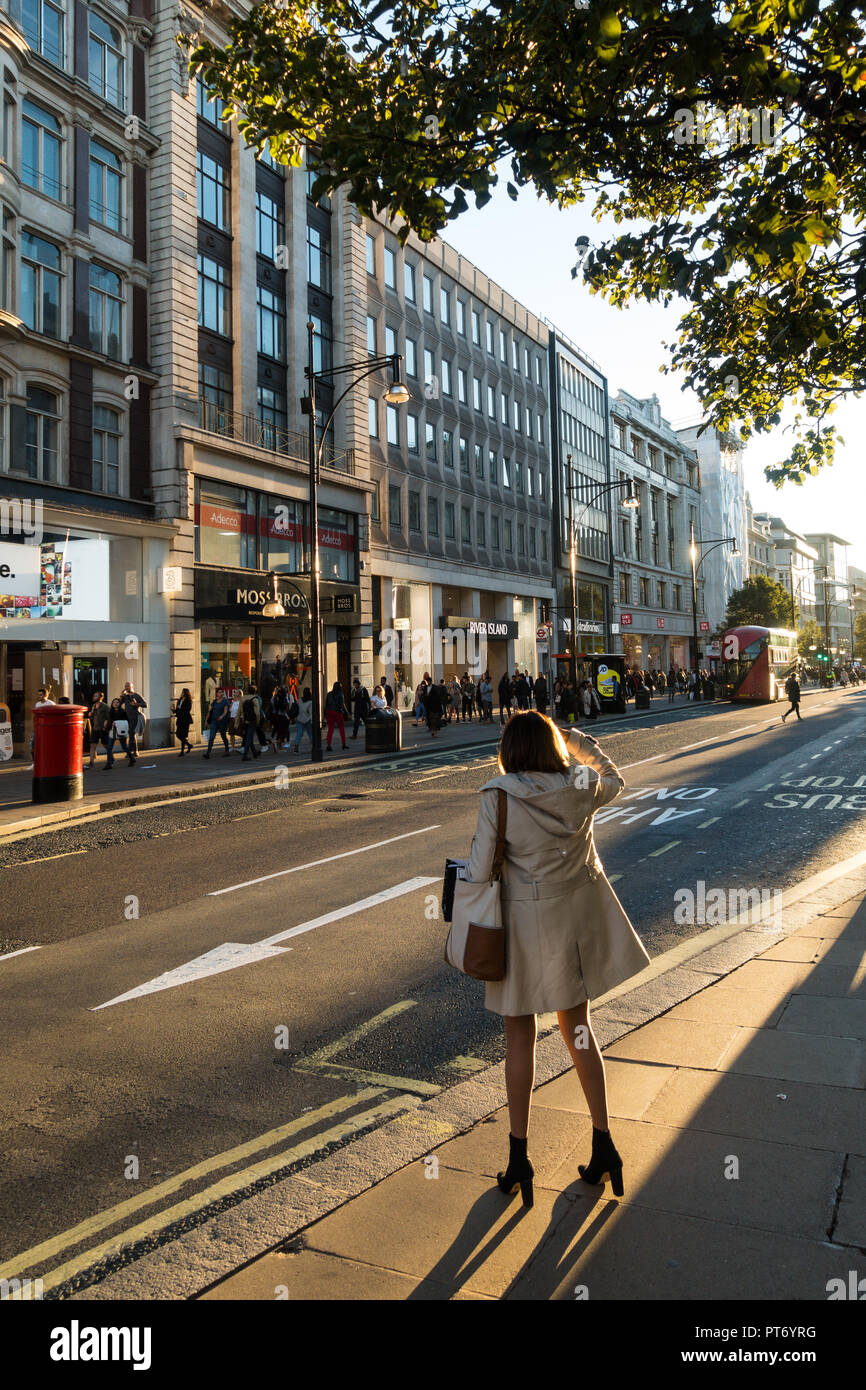 Woman hailing a cab on Oxford Street outside Moss Bros, River Island and the 3 shop, London, UK, Europe. Stock Photo
