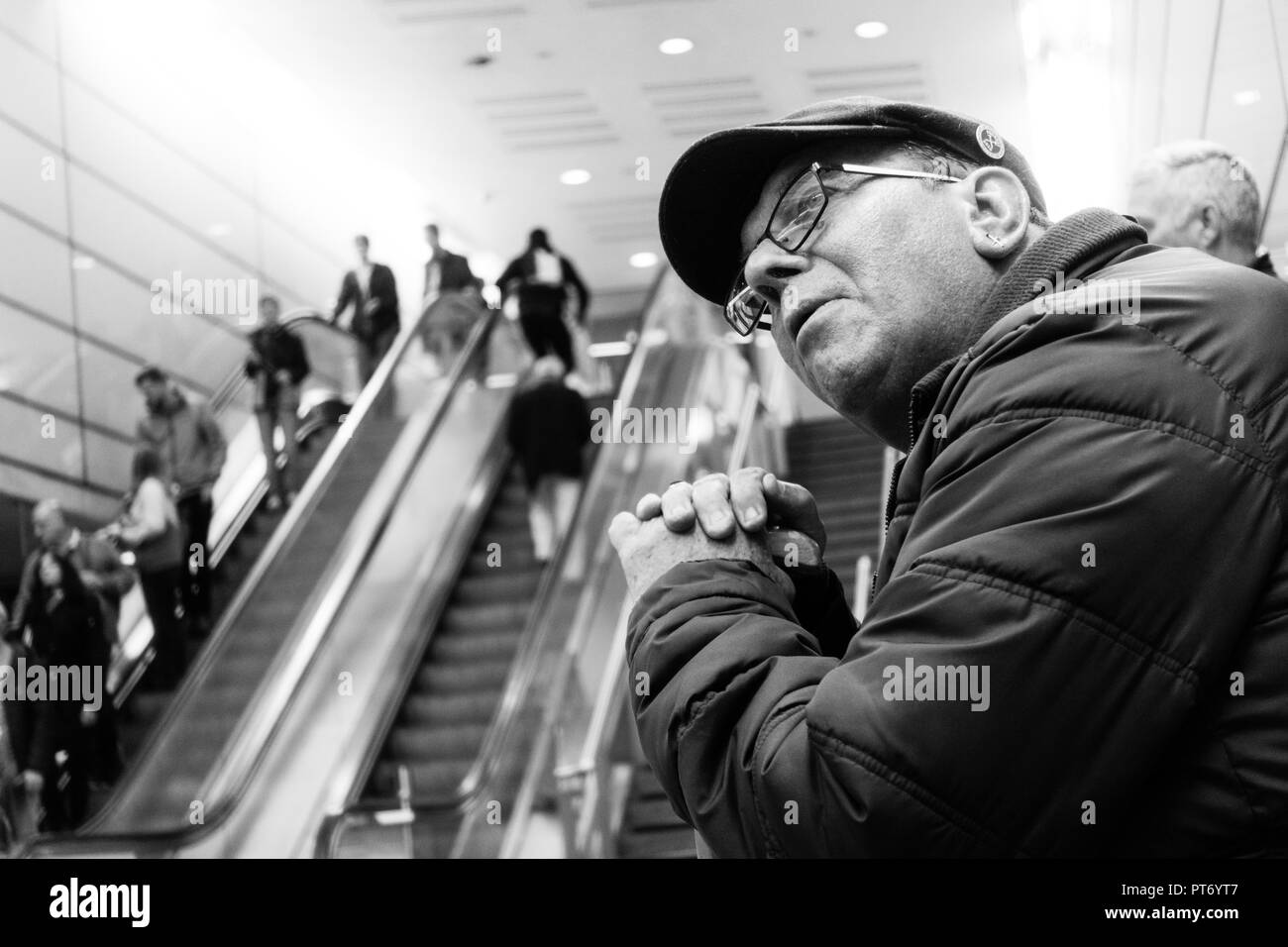 West Ham United Football Club fan waiting for a train wearing a flat cap and team badge, in black and white. Stock Photo