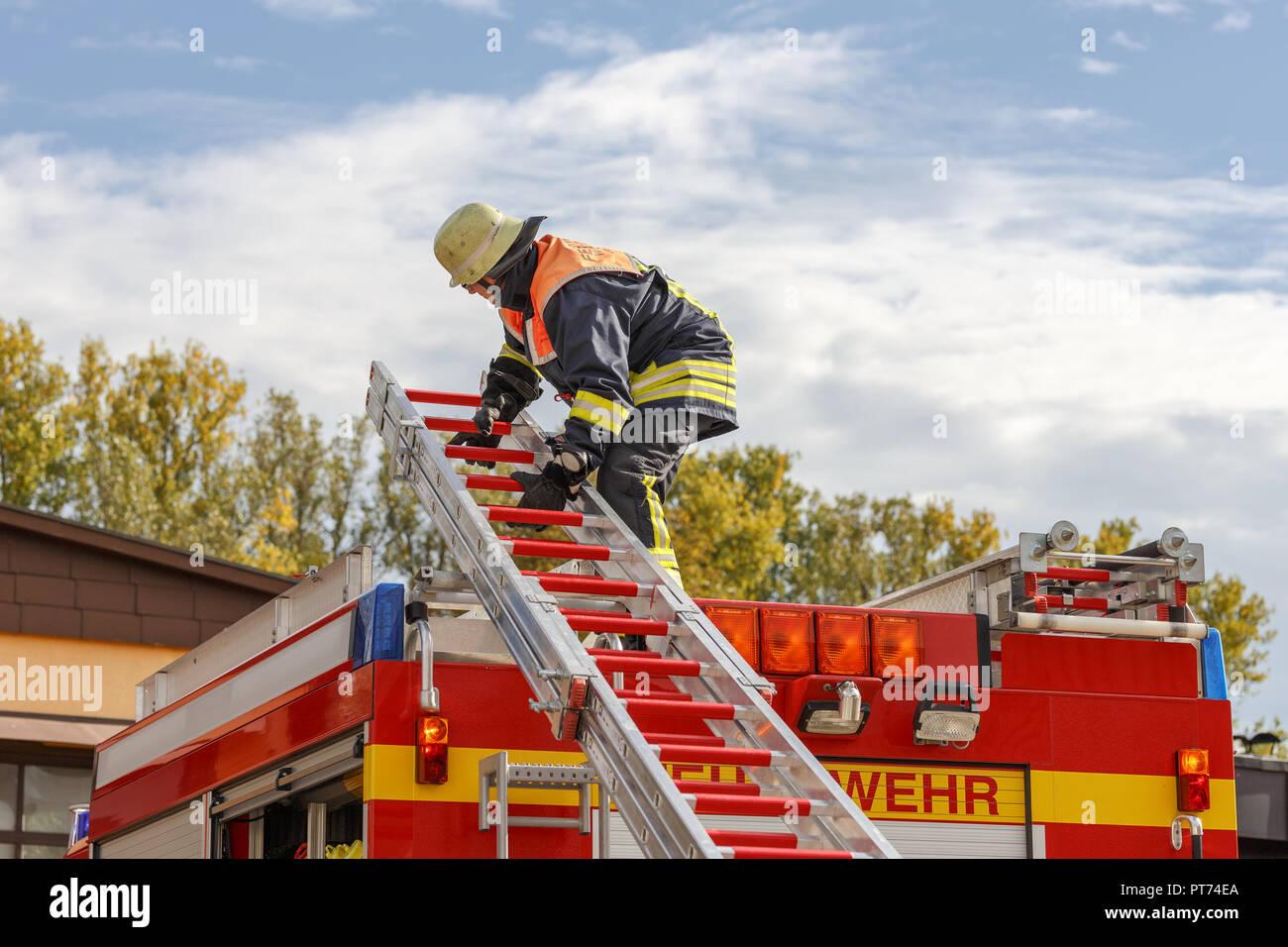 Feuerwehrmann beim abladen einer Leiter - Stock Image