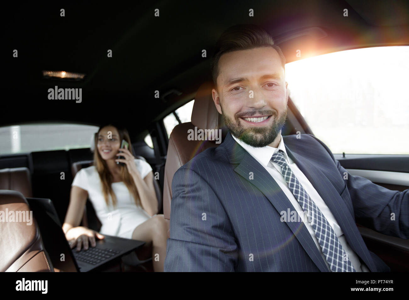 Young smiling handsome businessman in suit sitting in his luxurious car. Stock Photo