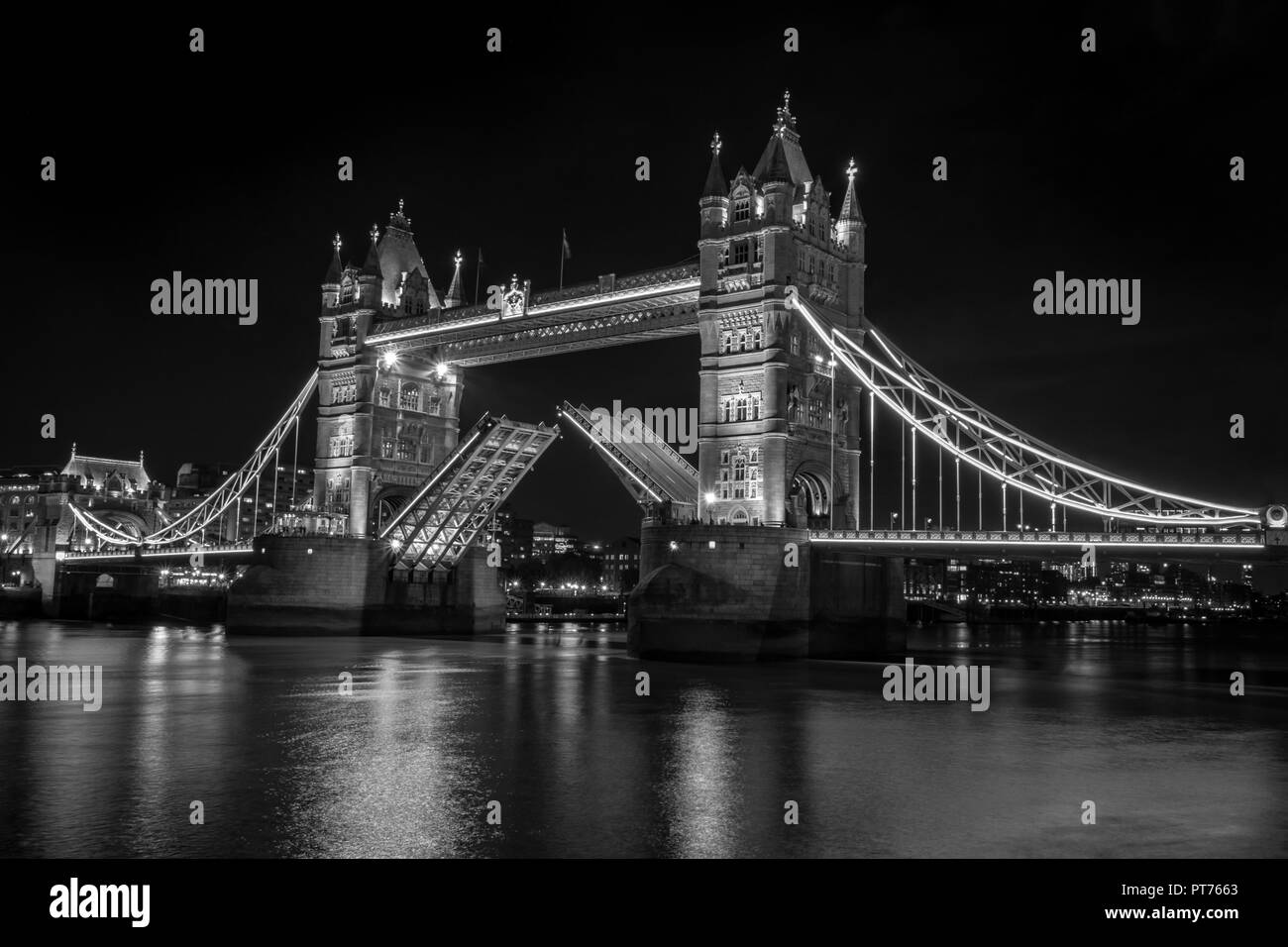 This is a black and white picture of Tower Bridge in London all light up at night - Stock Image