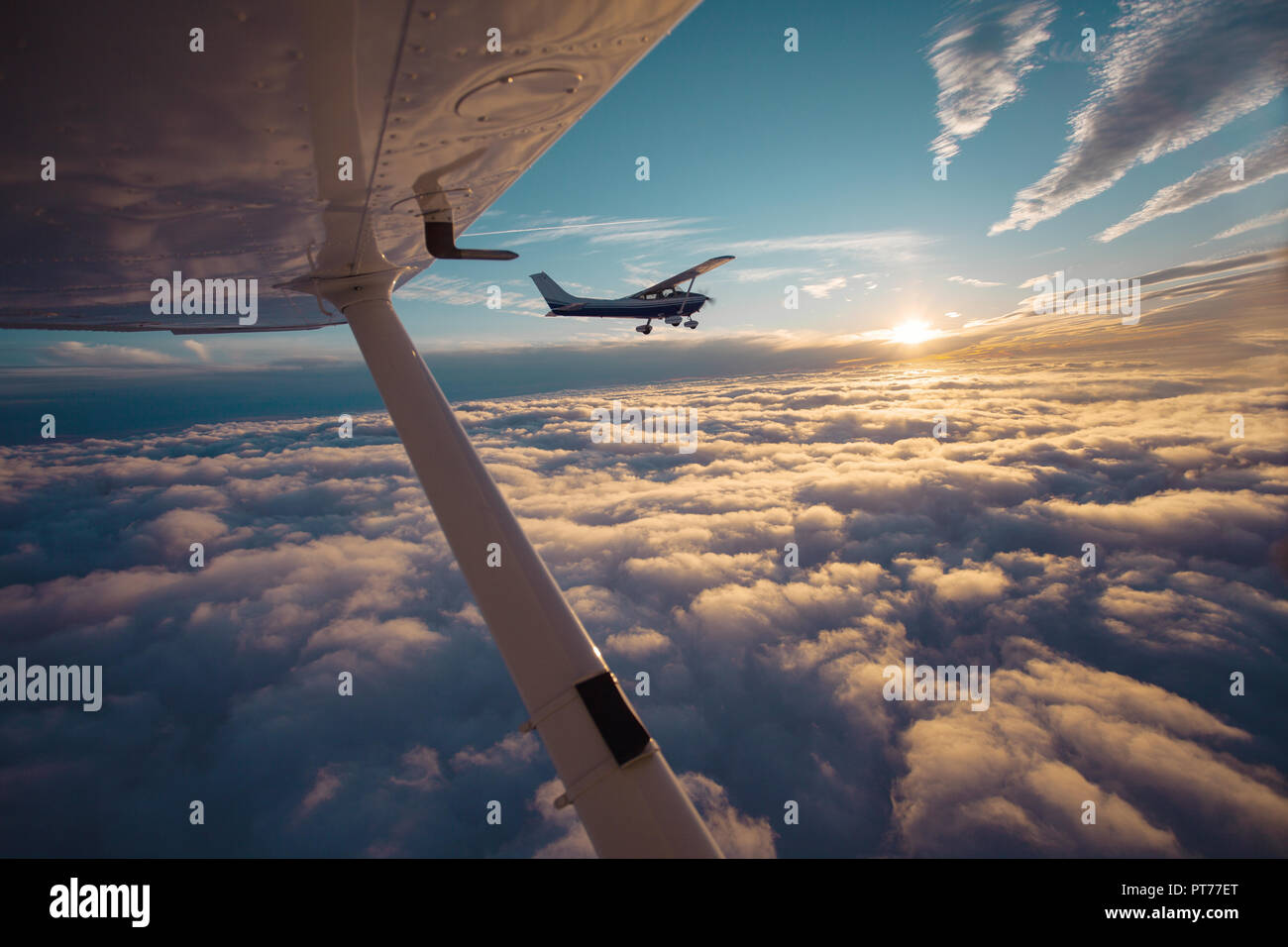 Small single engine airplane flying in the gorgeous sunset sky through the sea of clouds - Stock Image