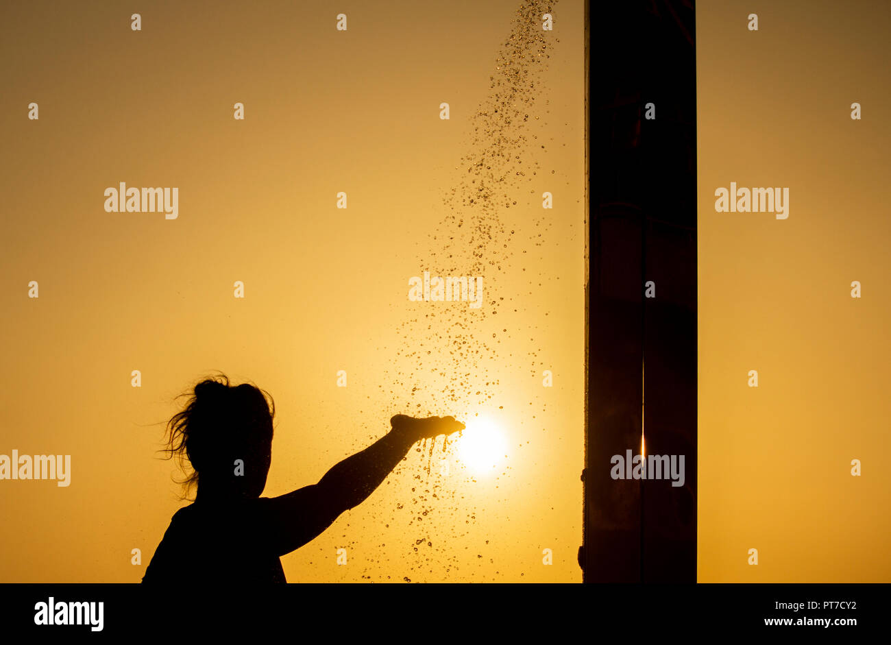 Female jogger cooling down under beach shower at sunrise during heatwave. - Stock Image