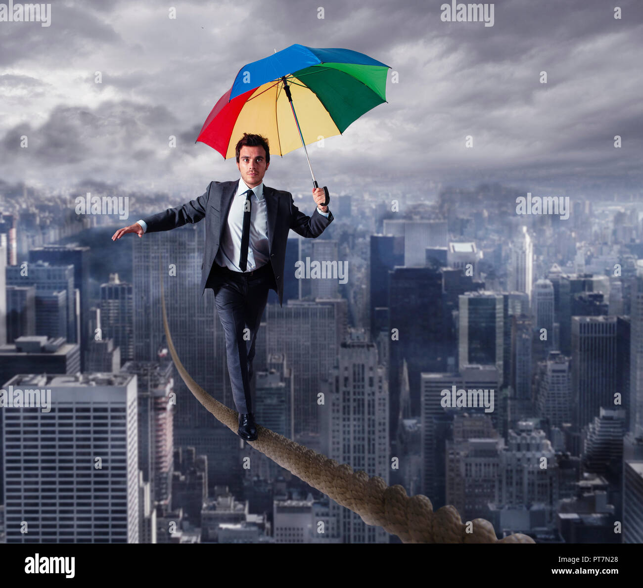 Equilibrist businessman walk on a rope with umbrella over the city. Concept of overcome the problems and positivity - Stock Image