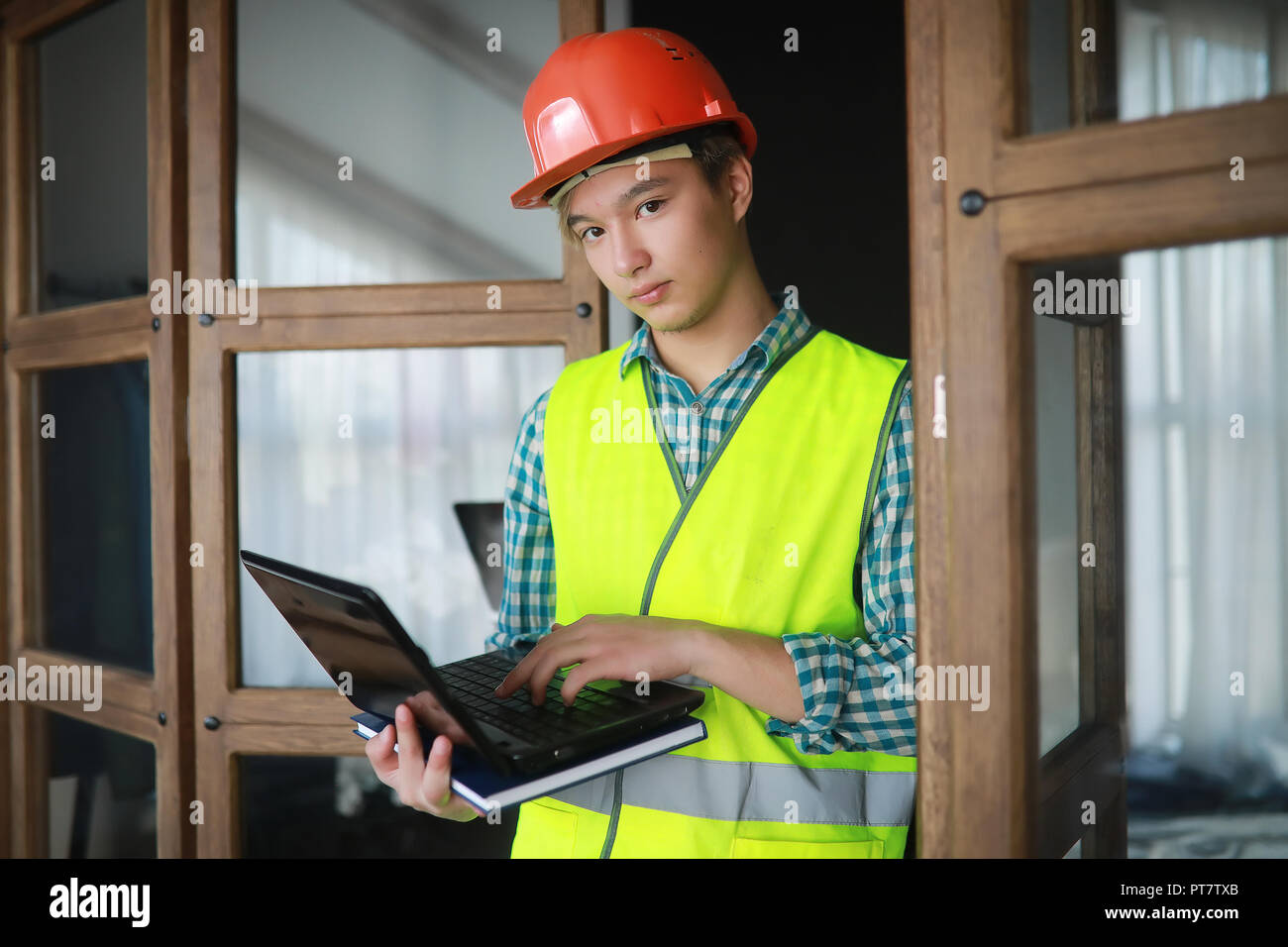 Asian man in protective helmet and construction waistcoat - Stock Image