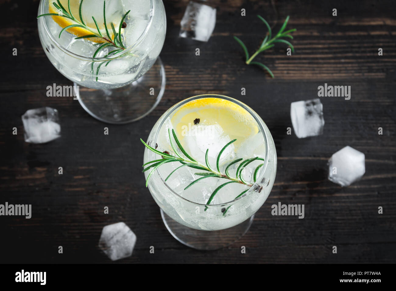 Alcohol drink (gin tonic cocktail) with lemon, rosemary and ice on rustic black wooden table, copy space, top view. Iced cocktail drink with lemon and - Stock Image