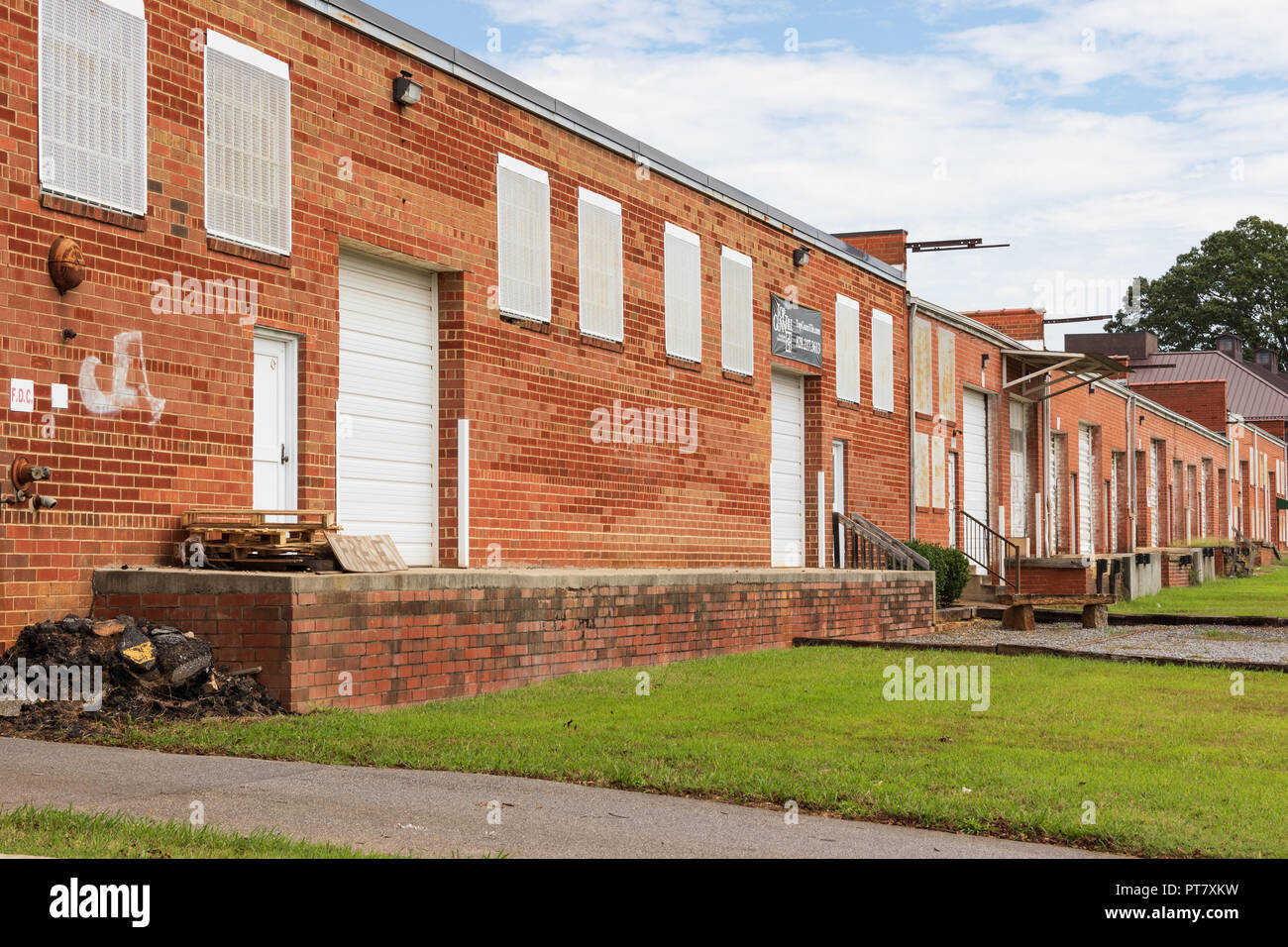 HICKORY, NC, USA-9/18/18:  A line of low loading docks and bay doors of an old industrial building. Stock Photo