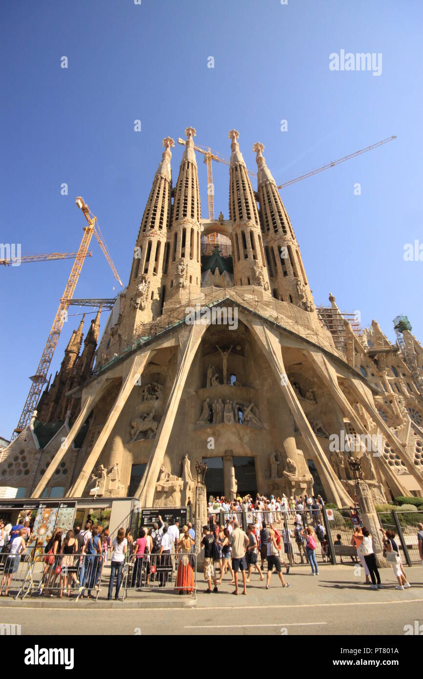 Tourists visitors and sightseers  in front of the unfinished church of Sagrada Família in the Spanish city of Barcelona Spain - Stock Image