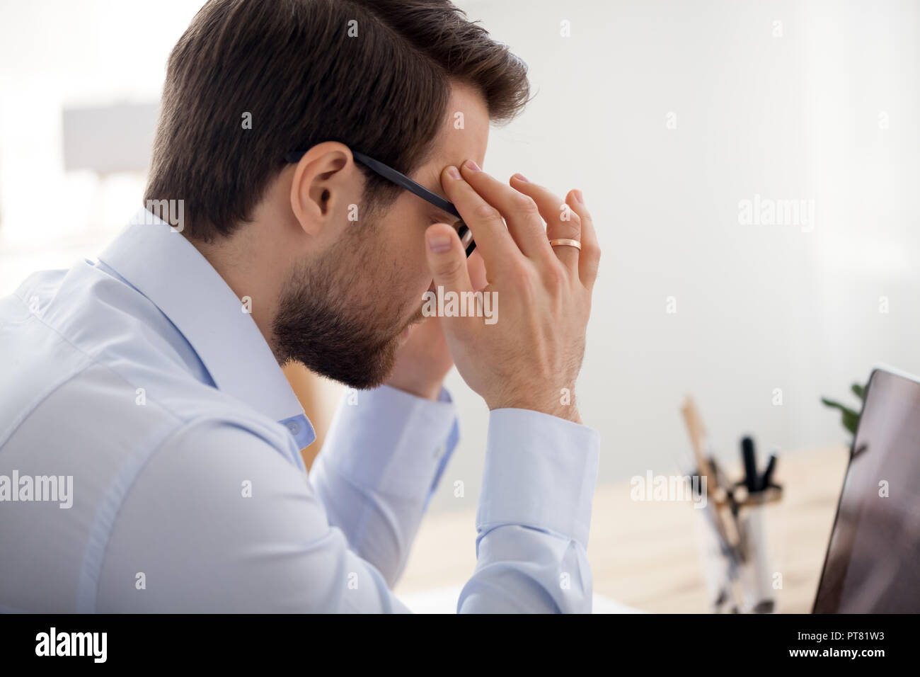 Fatigued business man with headache working in office - Stock Image