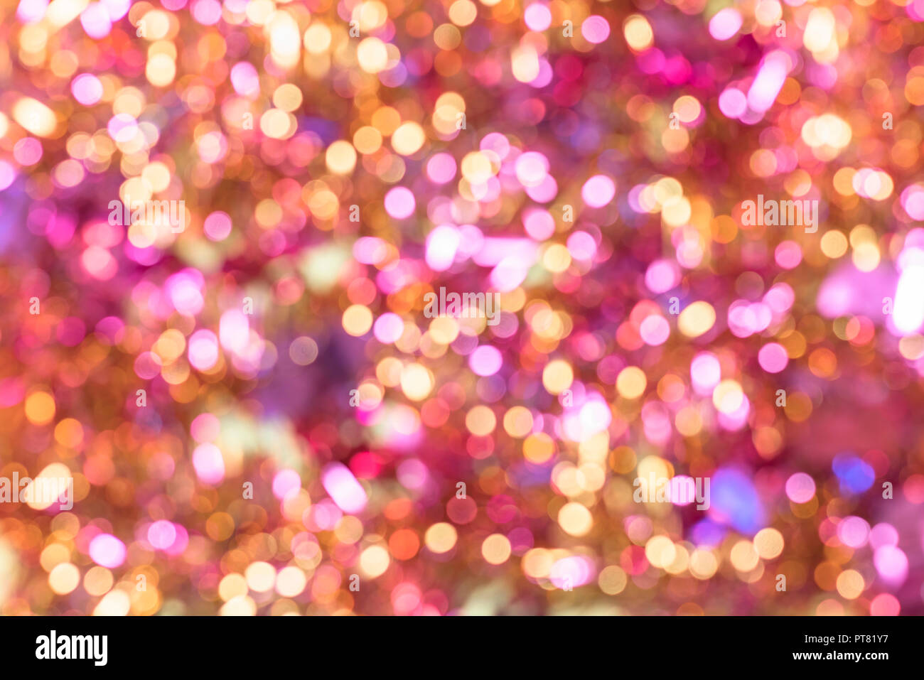 Background texture full of unsharp blurring golden yellow and cute pink shining bokeh lens aesthetic aberration effect. Stock Photo