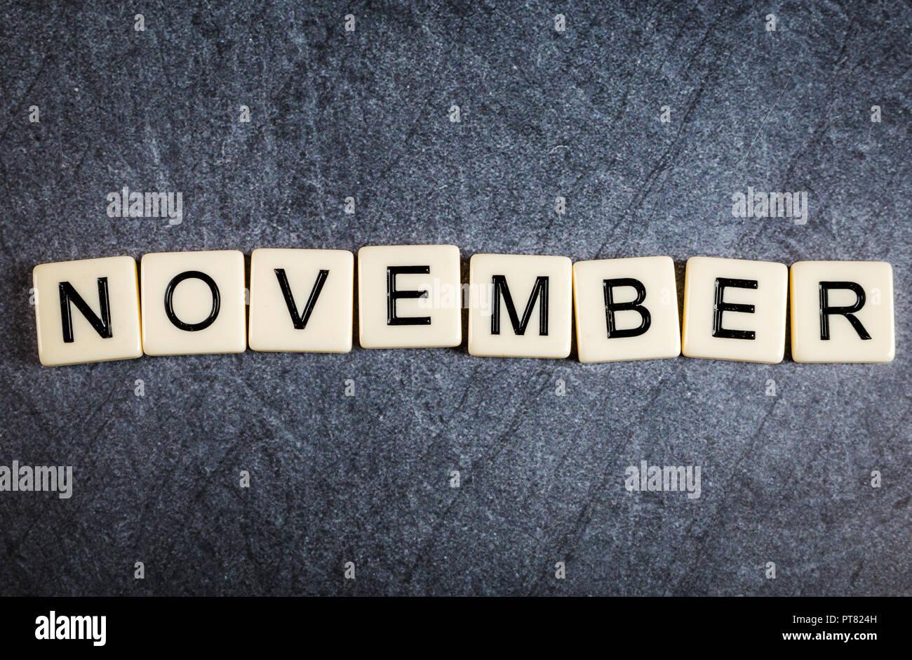 Letter tiles on black slate background spelling November