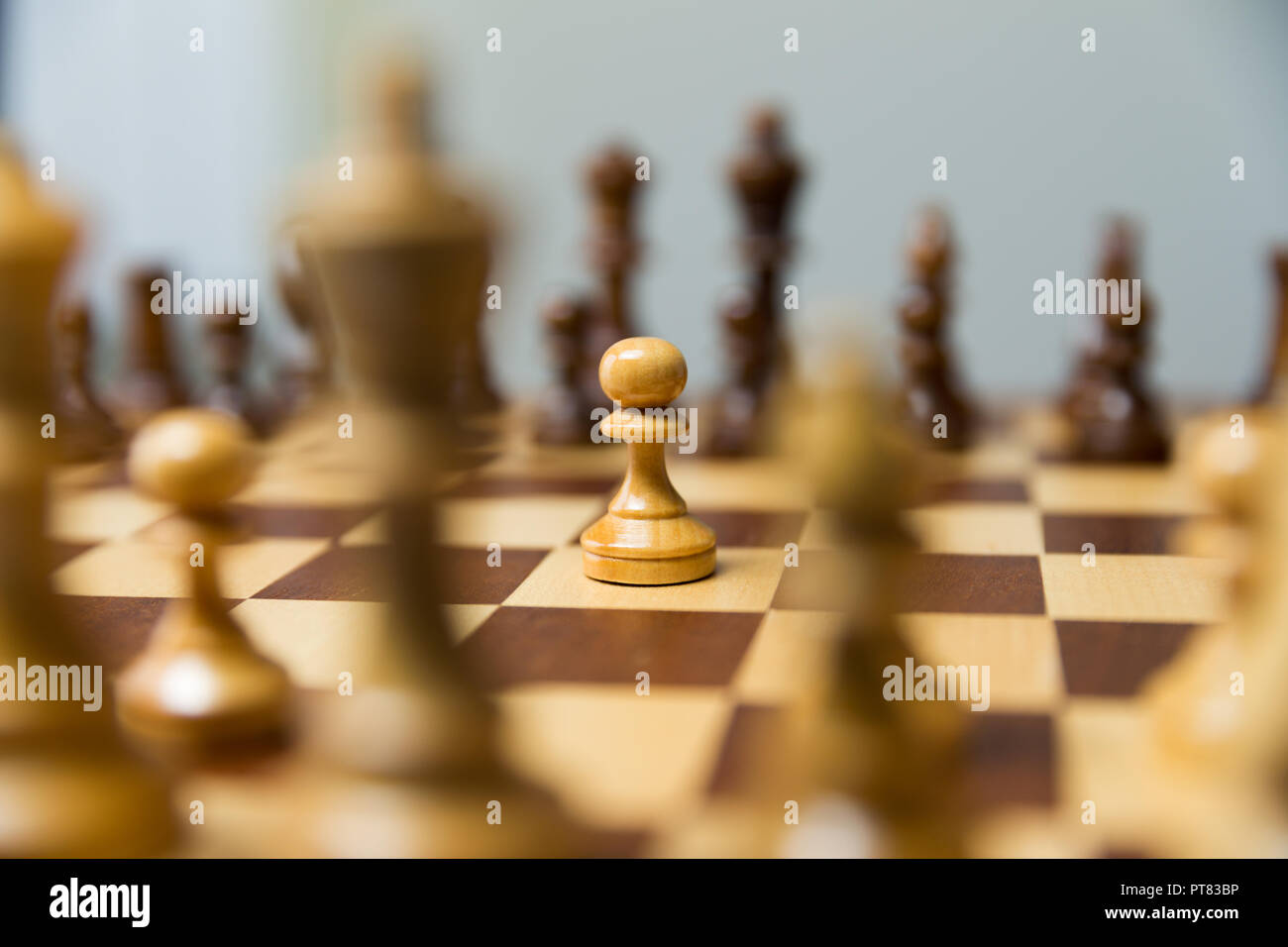 Pawn standing in the middle of chess board. Courage and leadership concept. - Stock Image