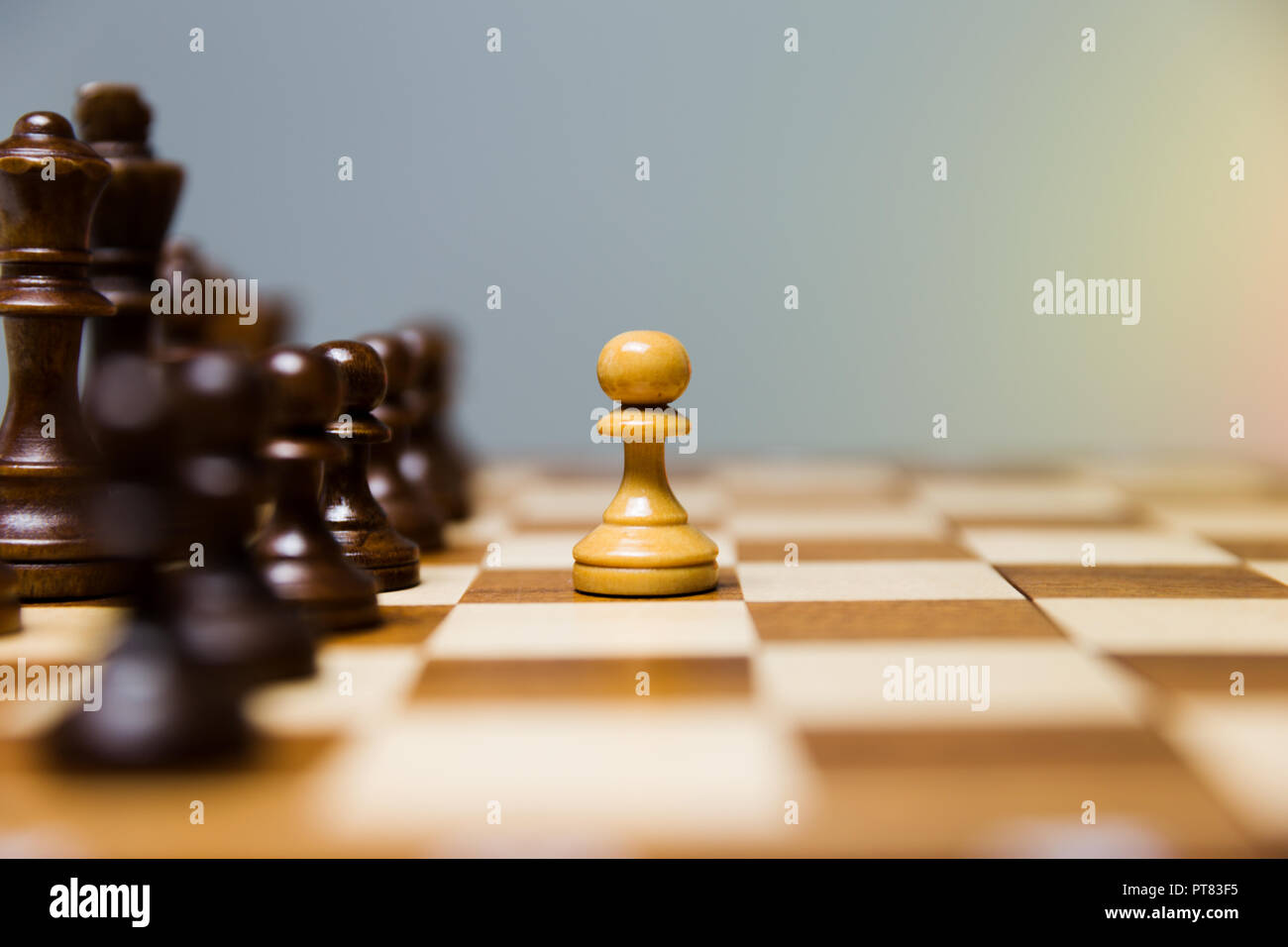 Pawn standing in front of aligned dark chess figures. Courage and leadership concept. - Stock Image