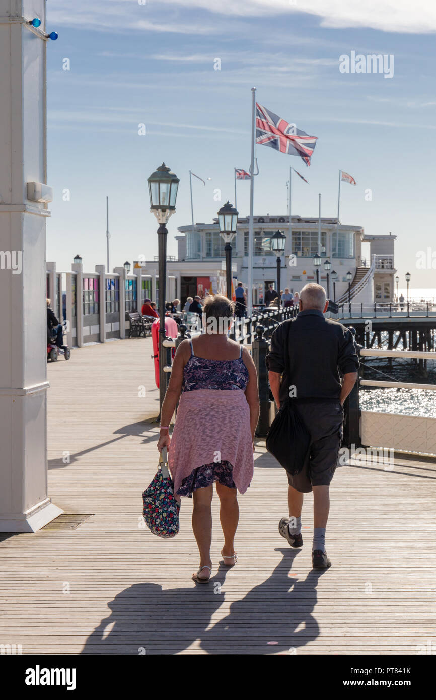 Worthing, Sussex, UK; 7th October 2018; A Couple Walk Away From the Camera Onto Worthing Pier.  A Union Jack Flies From a Flagpole - Stock Image