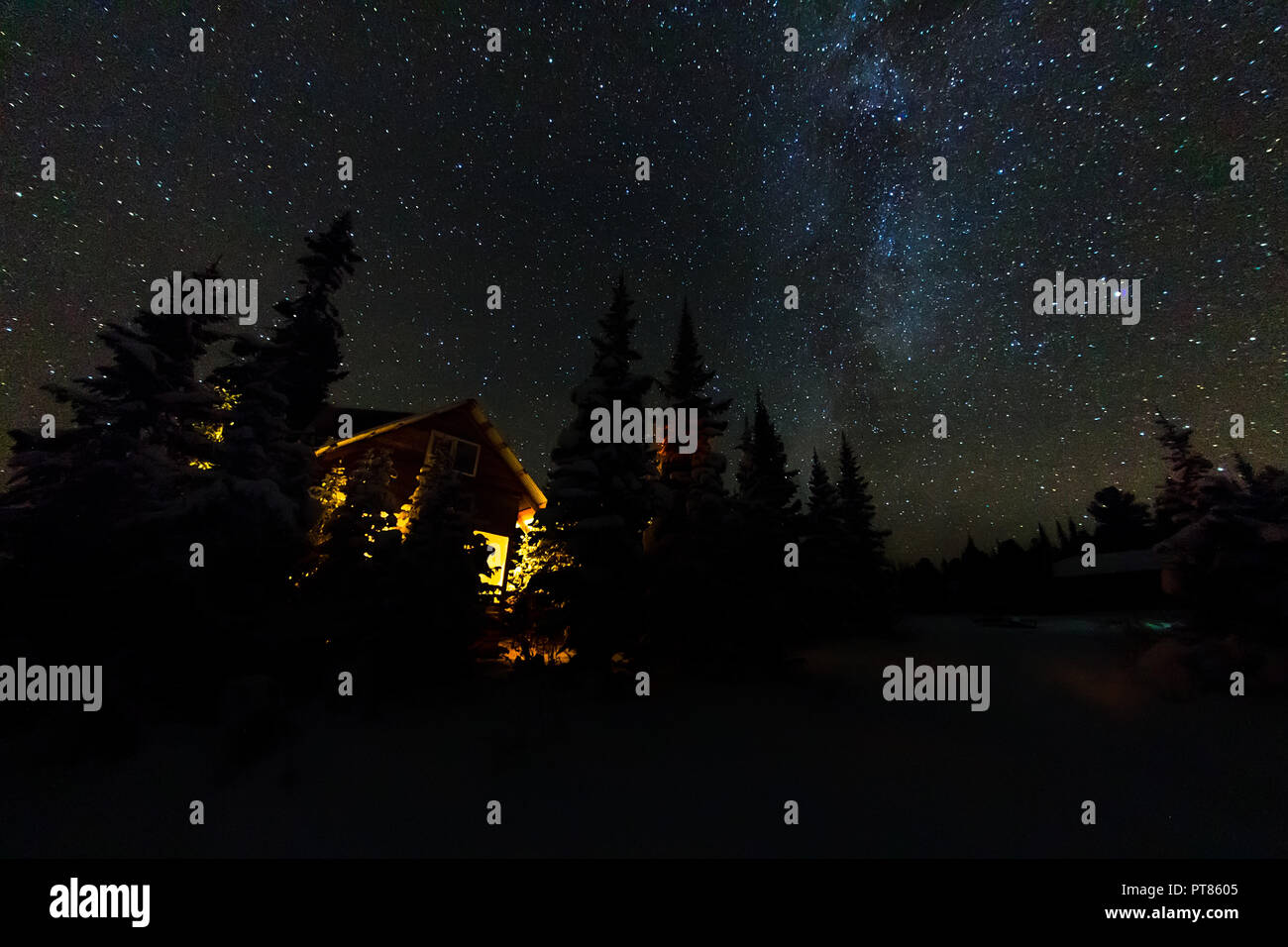 Light from the window of a forest hut under the night sky of the milky way in the winter forest. - Stock Image