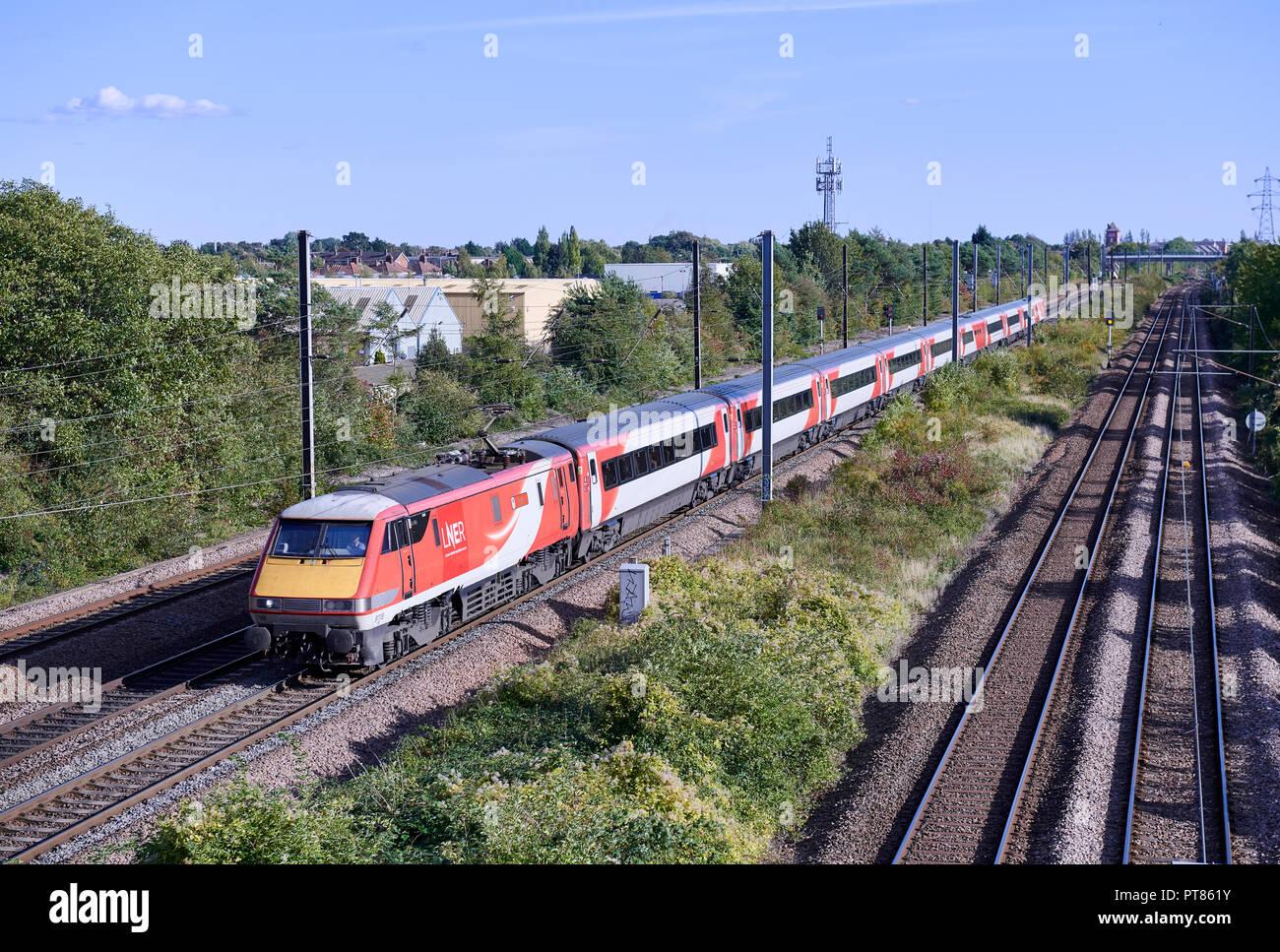 LNER Class 91 91118 heads 1S19 1330 London Kings Cross to Edinburgh service through Werrington Junction on the East Coast Mainline on 24/09/18. - Stock Image
