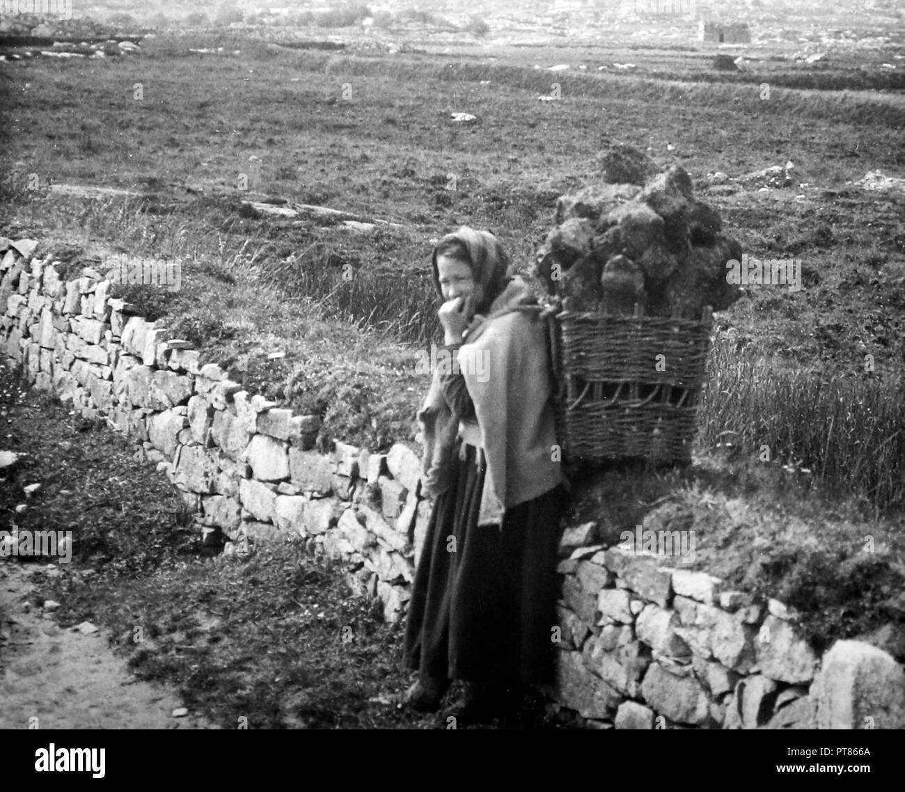 Carrying turf in a creel, West of Ireland, early 1900s - Stock Image