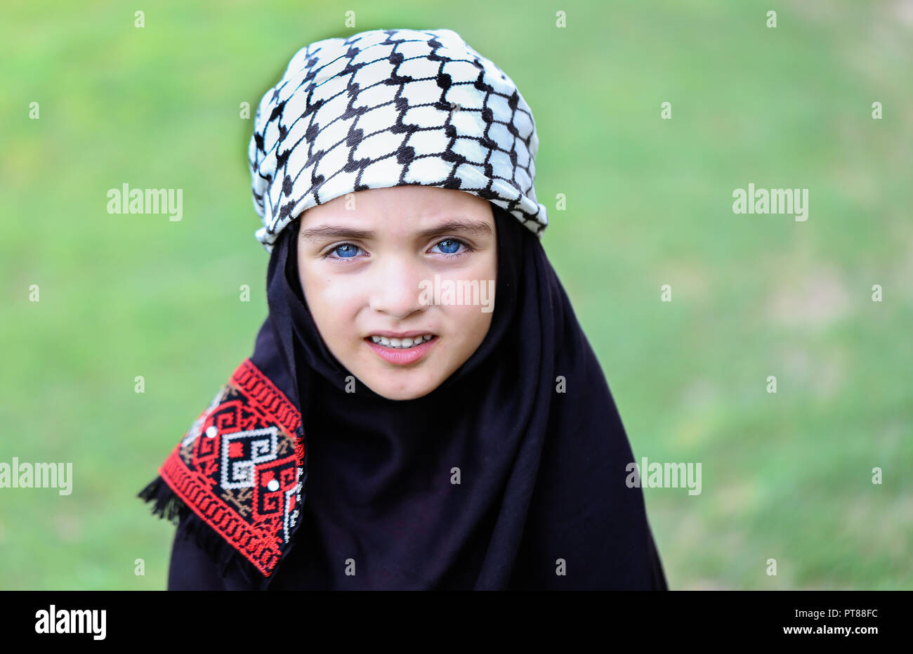 A photo of Palestinian girl with a traditional Arab Keffiyeh scarf on her head. - Stock Image