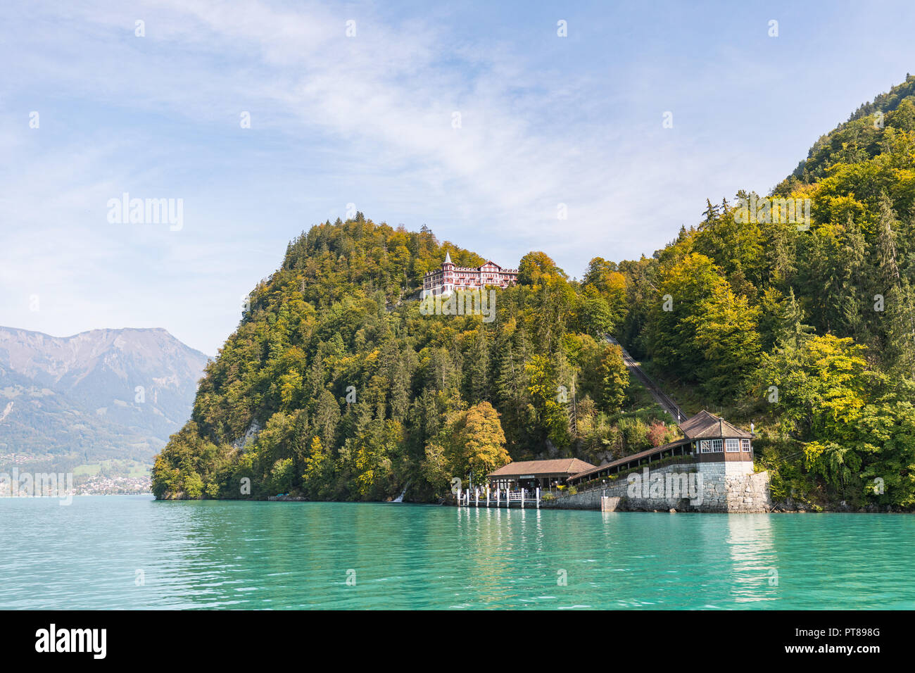 View from a boat over the turquoise lake Brienz to grand hotel giessbach in switzerland Stock Photo