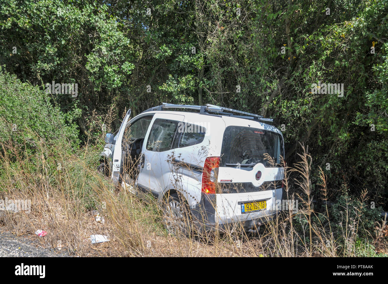 Car in a ditch on the side of the road after the driver had lost control - Stock Image