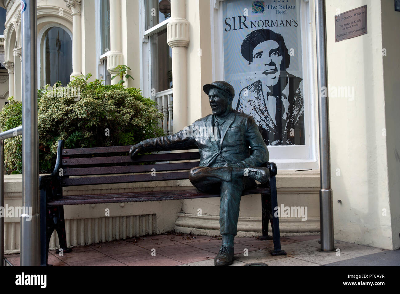 Statue of Sir Norman Wisdom sitting on a bench outside The Sefton Hotel, Douglas, Isle of Man - Stock Image