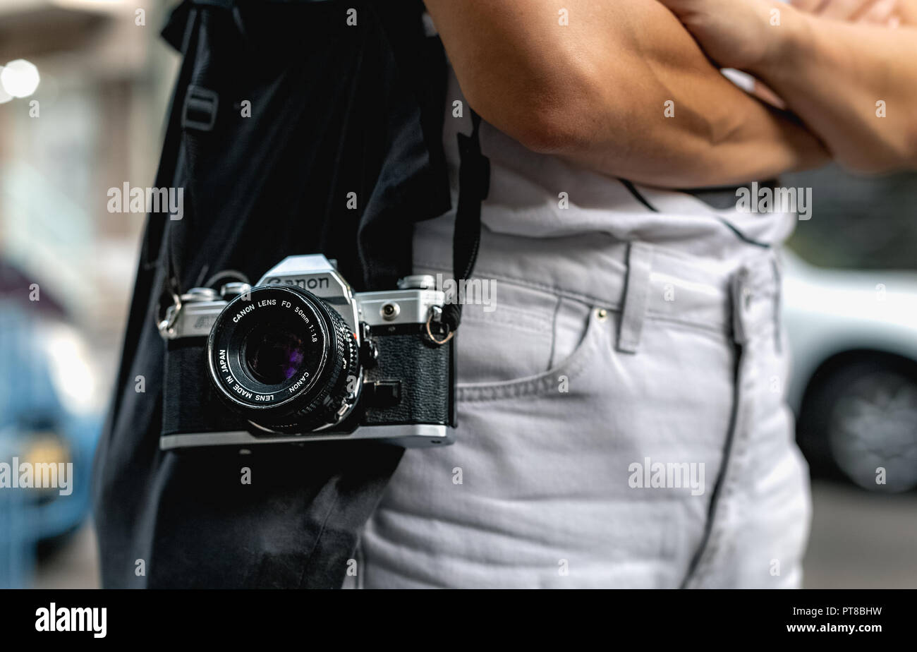 Young old school photographer with old Canon AE-1 35mm SLR film camera and Canon FD 50mm lens at street in Tel Aviv, Israel - Stock Image
