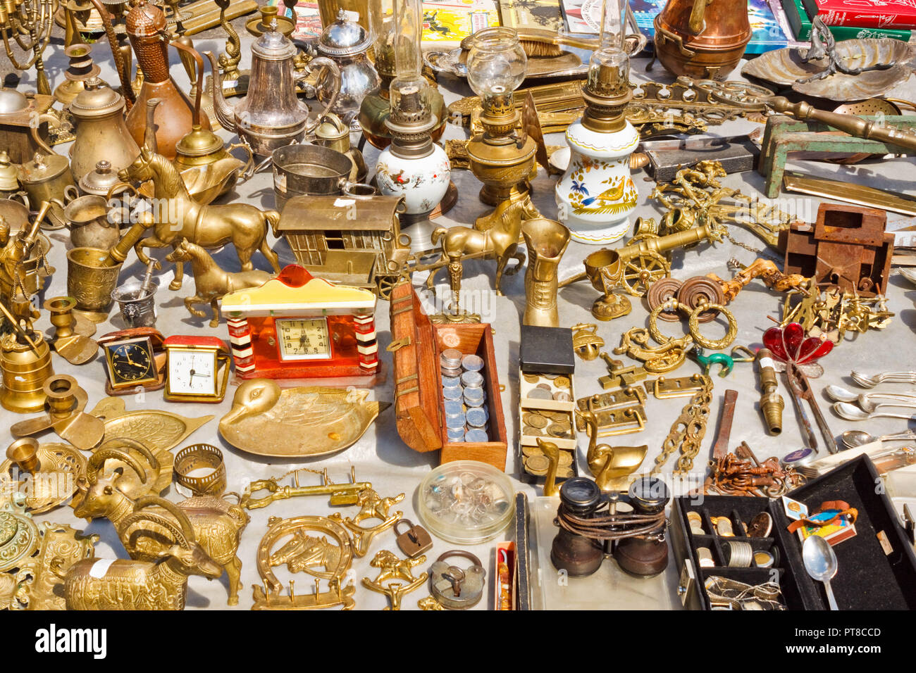 Lviv, Ukraine - July 10, 2015: Various things made of yellow metals for sale on a flea market. Decorative figurines, coins, lamps and other old and vi Stock Photo