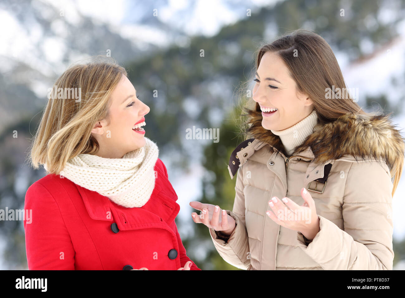 Two happy women warmly clothed talking in winter holiday in the mountain - Stock Image