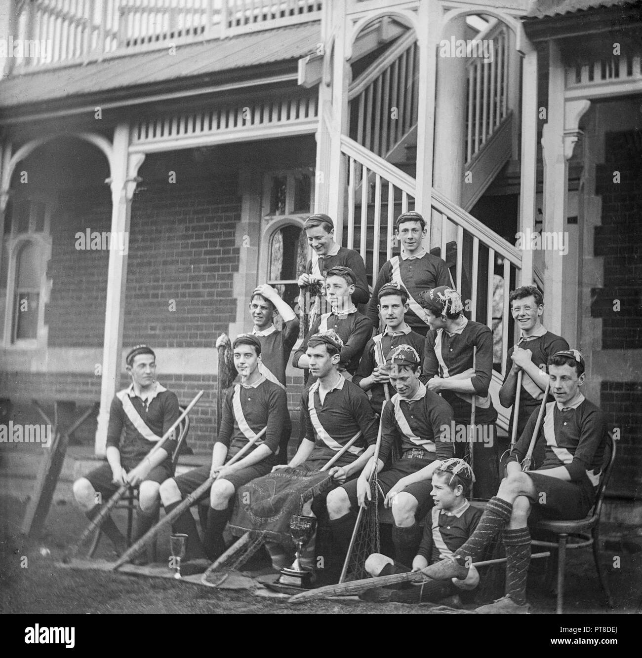 A late 19th or early 20th century black and white photograph showing a boys lacrosse team displaying two trophies