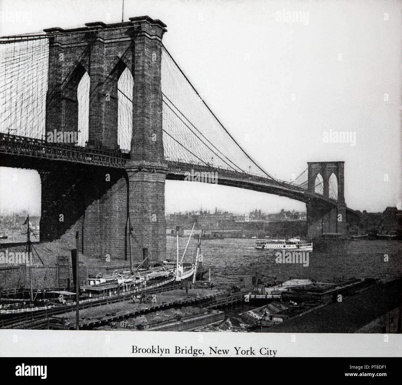 A late 19th or early 20th century black and white photograph of the brooklyn bridge in new york usa
