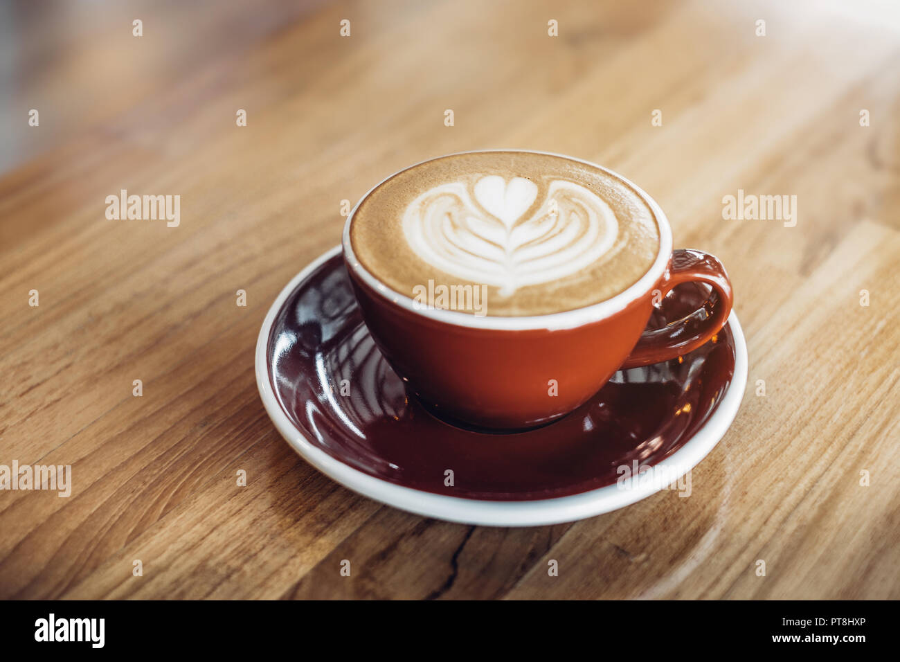 Close up hot cappuccino red coffee cup with heart shape latte art on wood table at cafe,Drak tone filter,food and drink Stock Photo