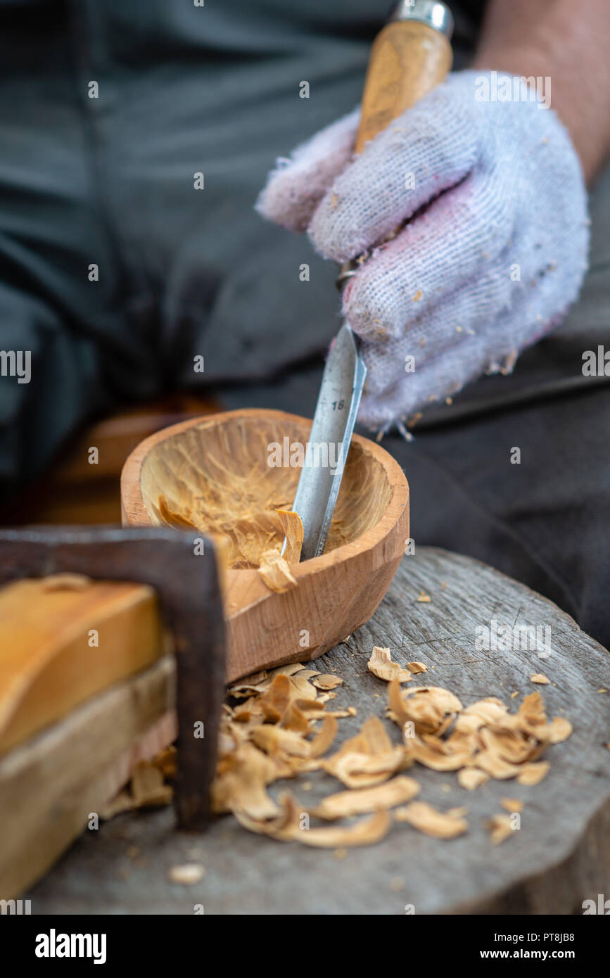 Craftsman demonstrates the process of making wooden spoons handmade using tools. National crafts concept. - Stock Image