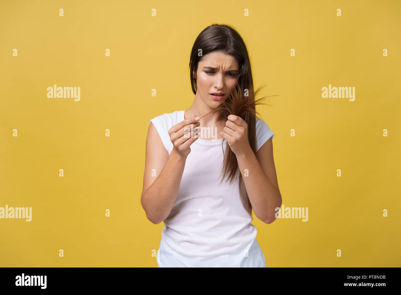 Woman hand holding her long hair with looking at damaged splitting ends of hair care problems. - Stock Image